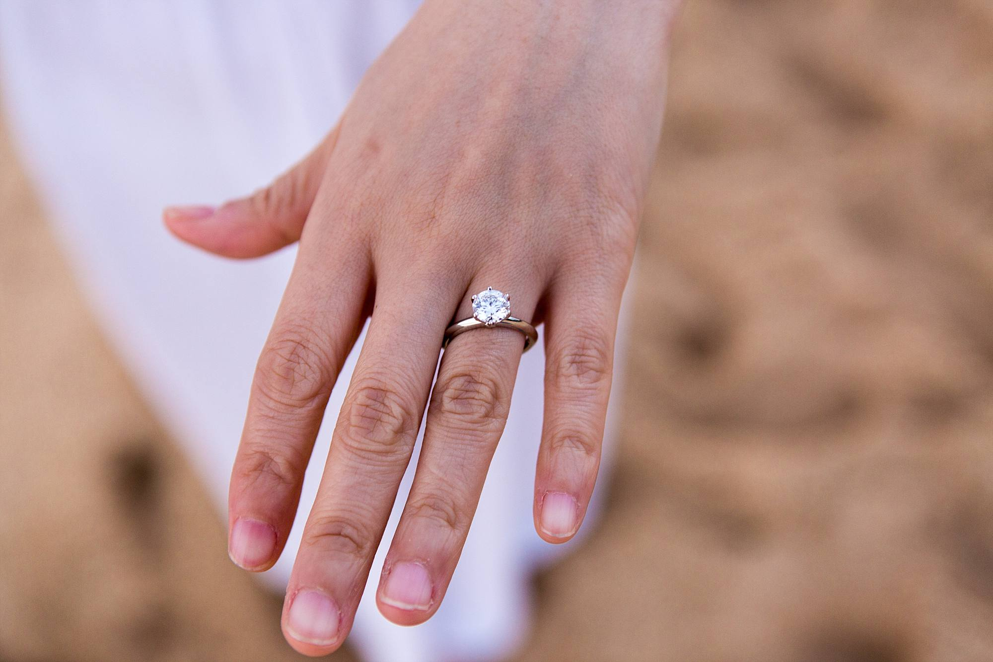 hand with solitaire engagement ring