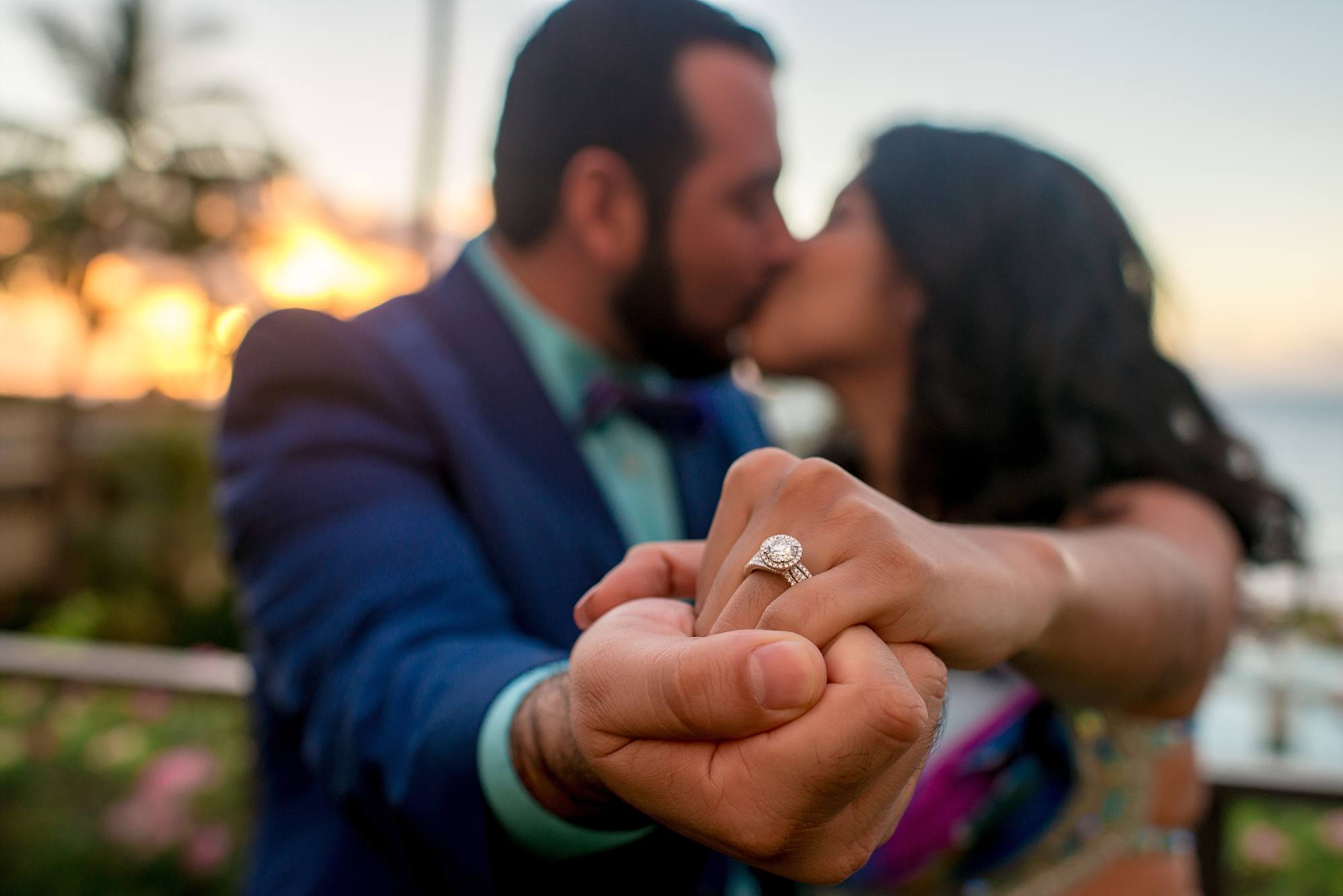 couple kissing holding out hand with engagement ring on it