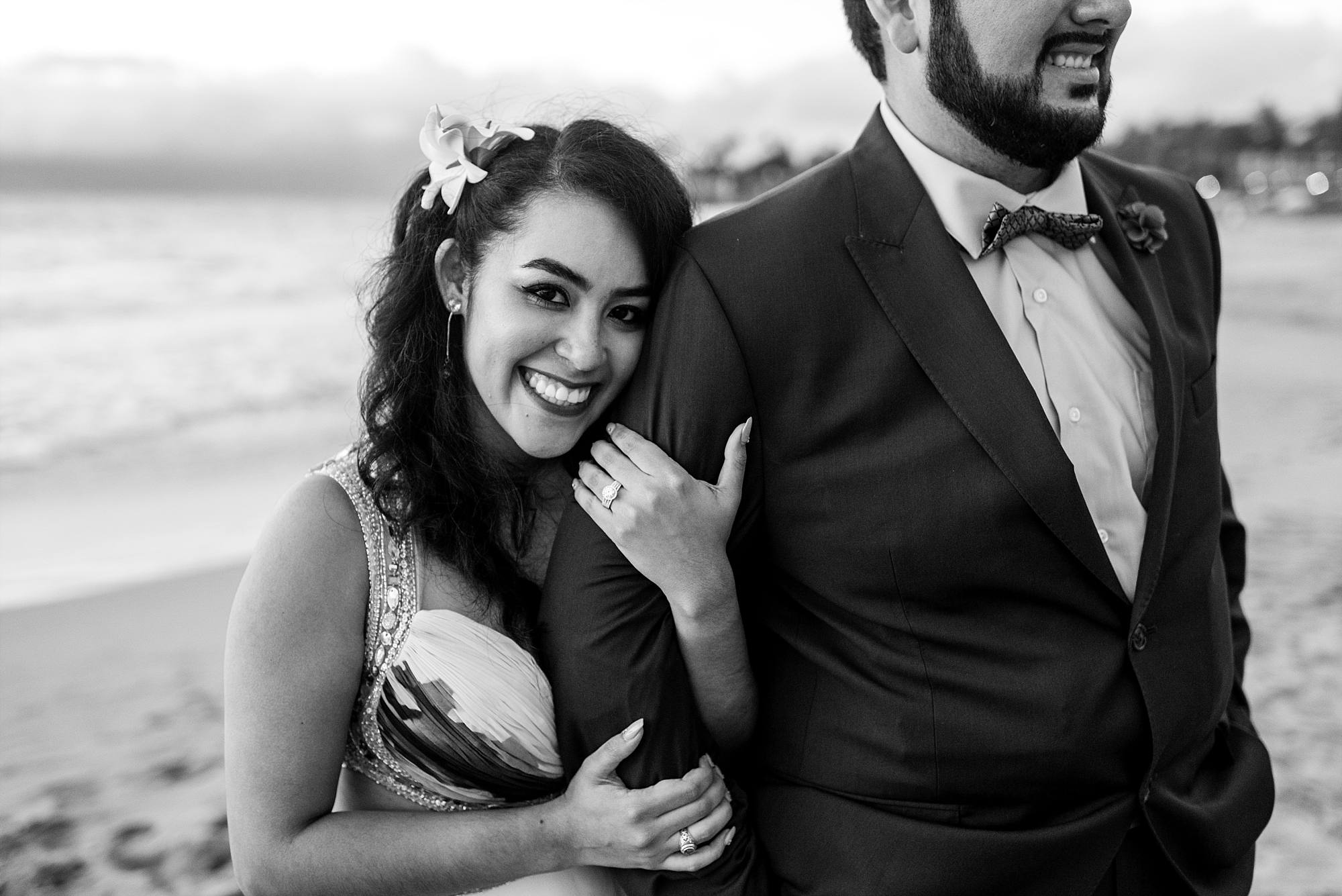 woman holding fiance's arm, smiling at the camera