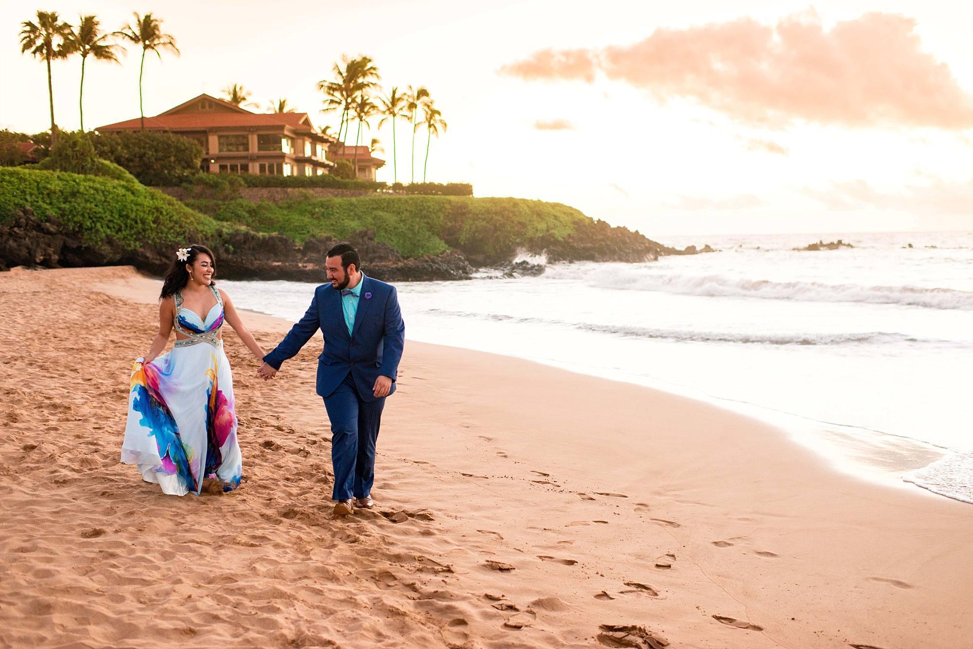 couple walking down beach at four seasons maui