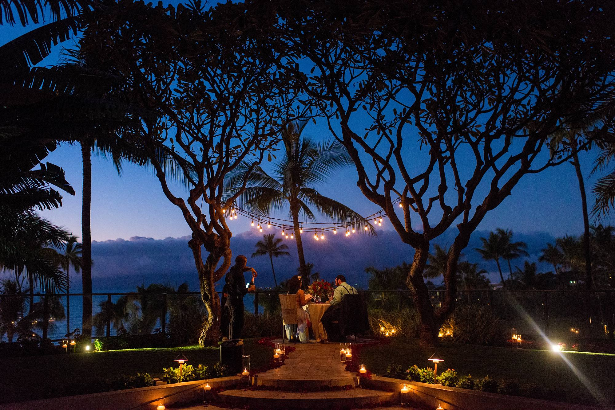 couuple at romantic table set at the top of the stairs at the Four Seasons Maui