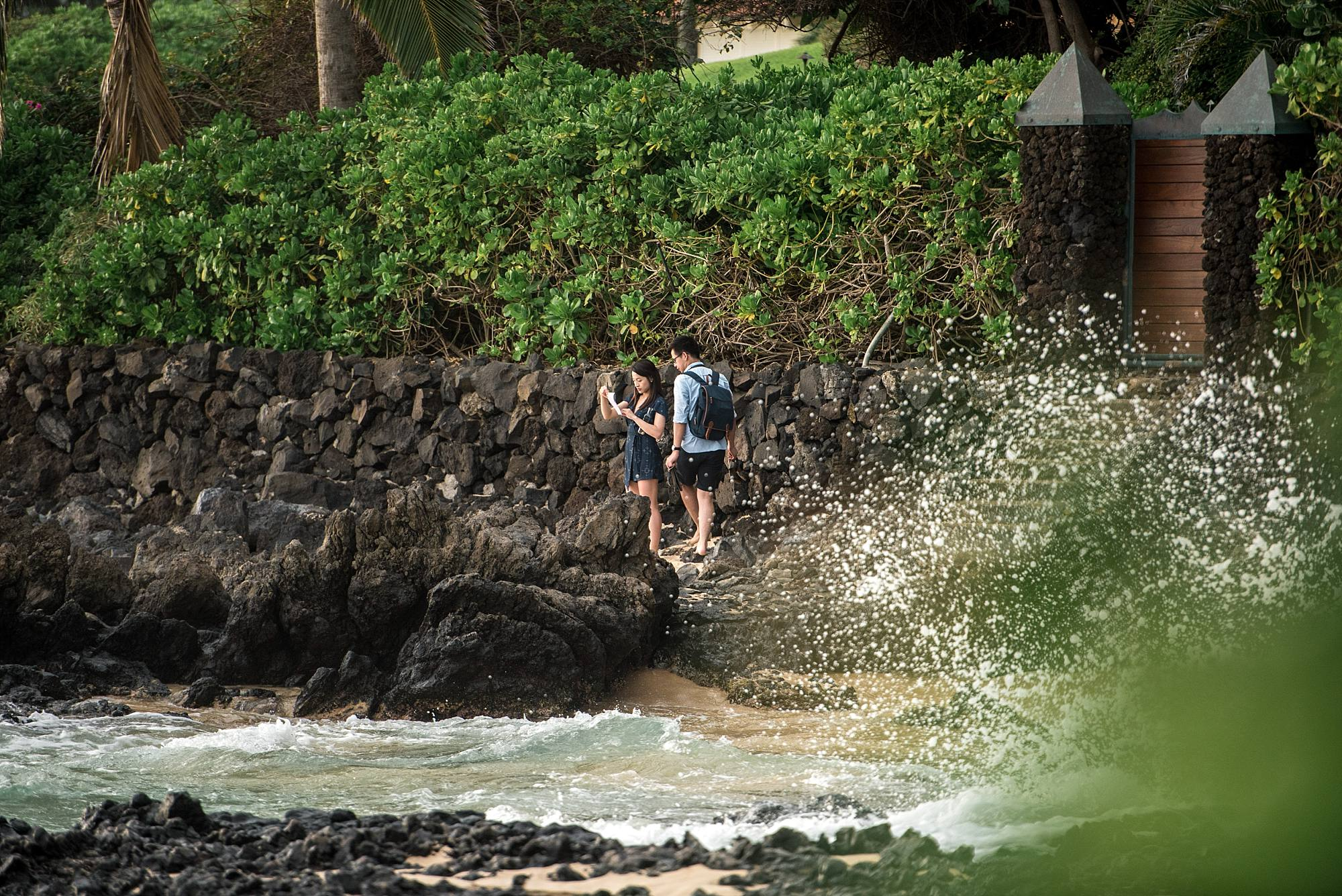 couple finding scavenger hunt clue with water splashing off lava rocks