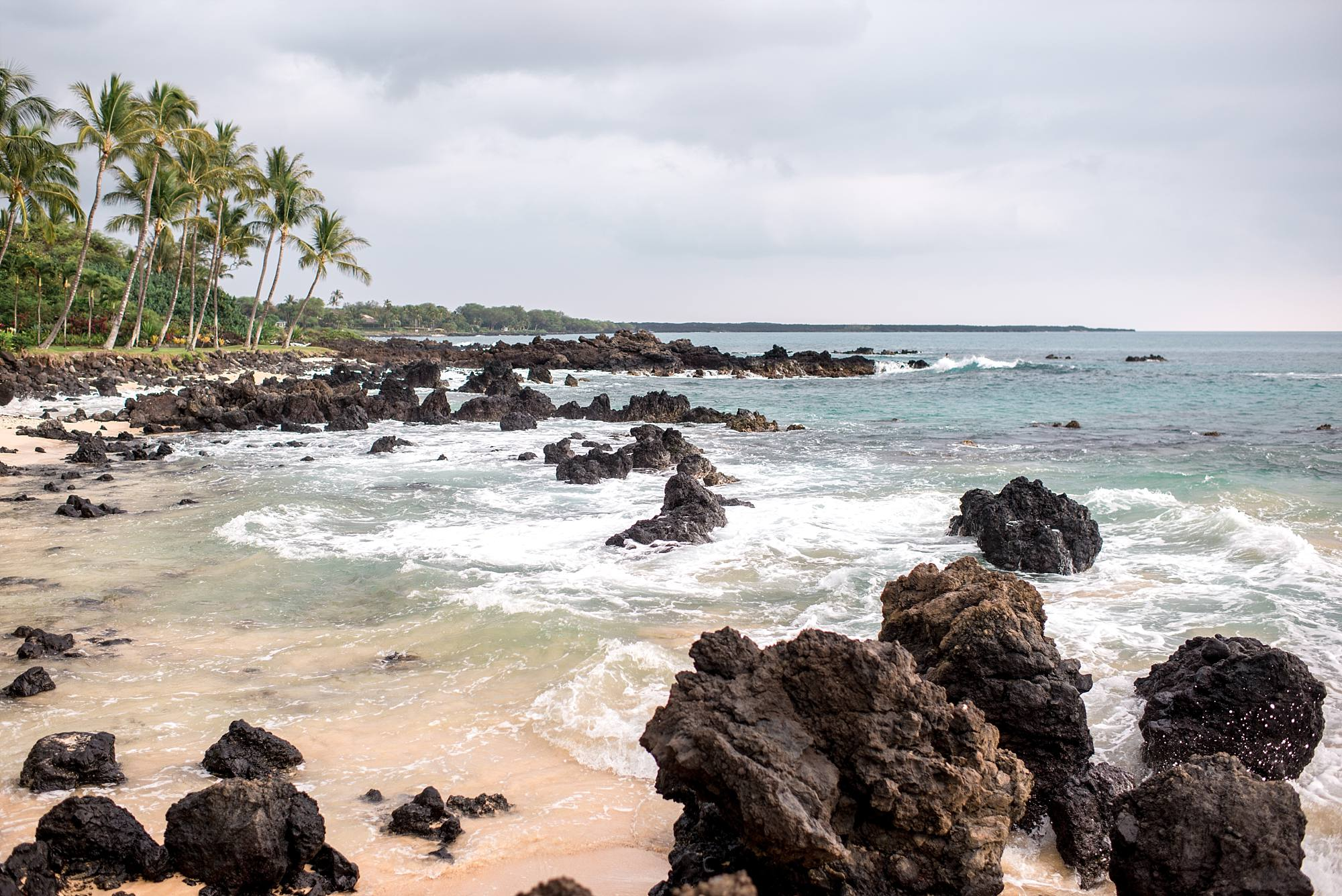 South Maui beach with black rocks and palm trees