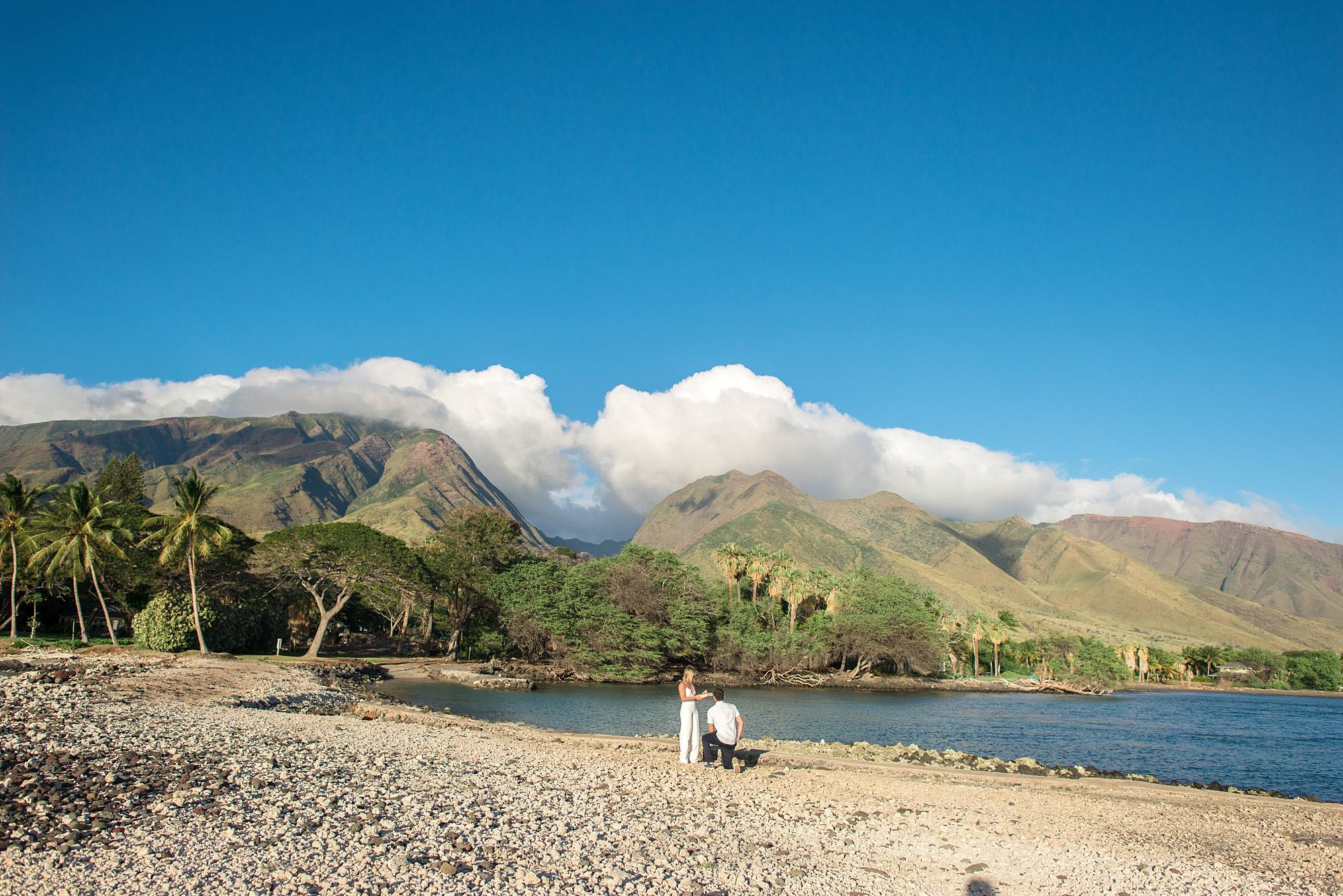 West Maui Mountains in the background and man proposing to woman