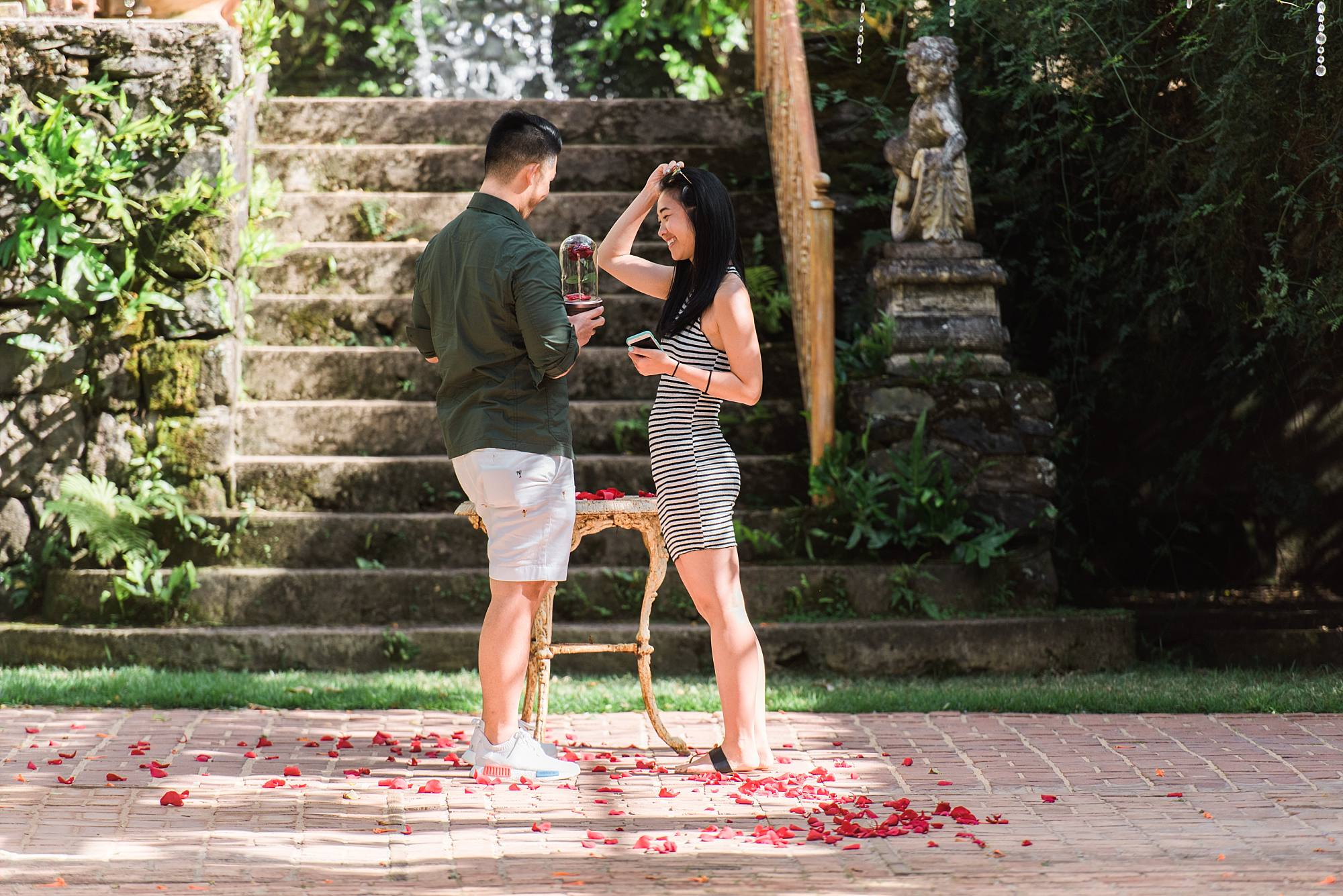 Man lifting up glass covered rose to show his girlfried