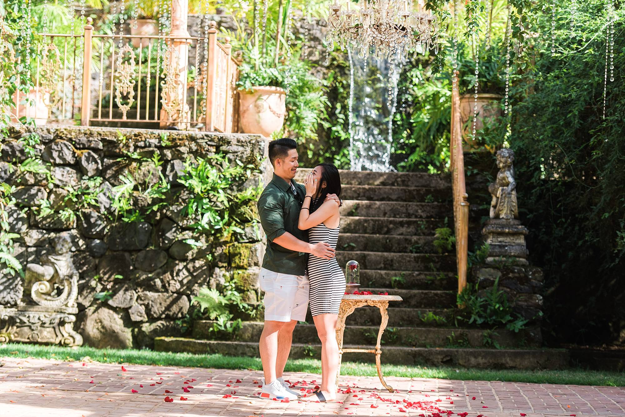 Woman crying and hugging her new fiance with waterfall and greenery behind them