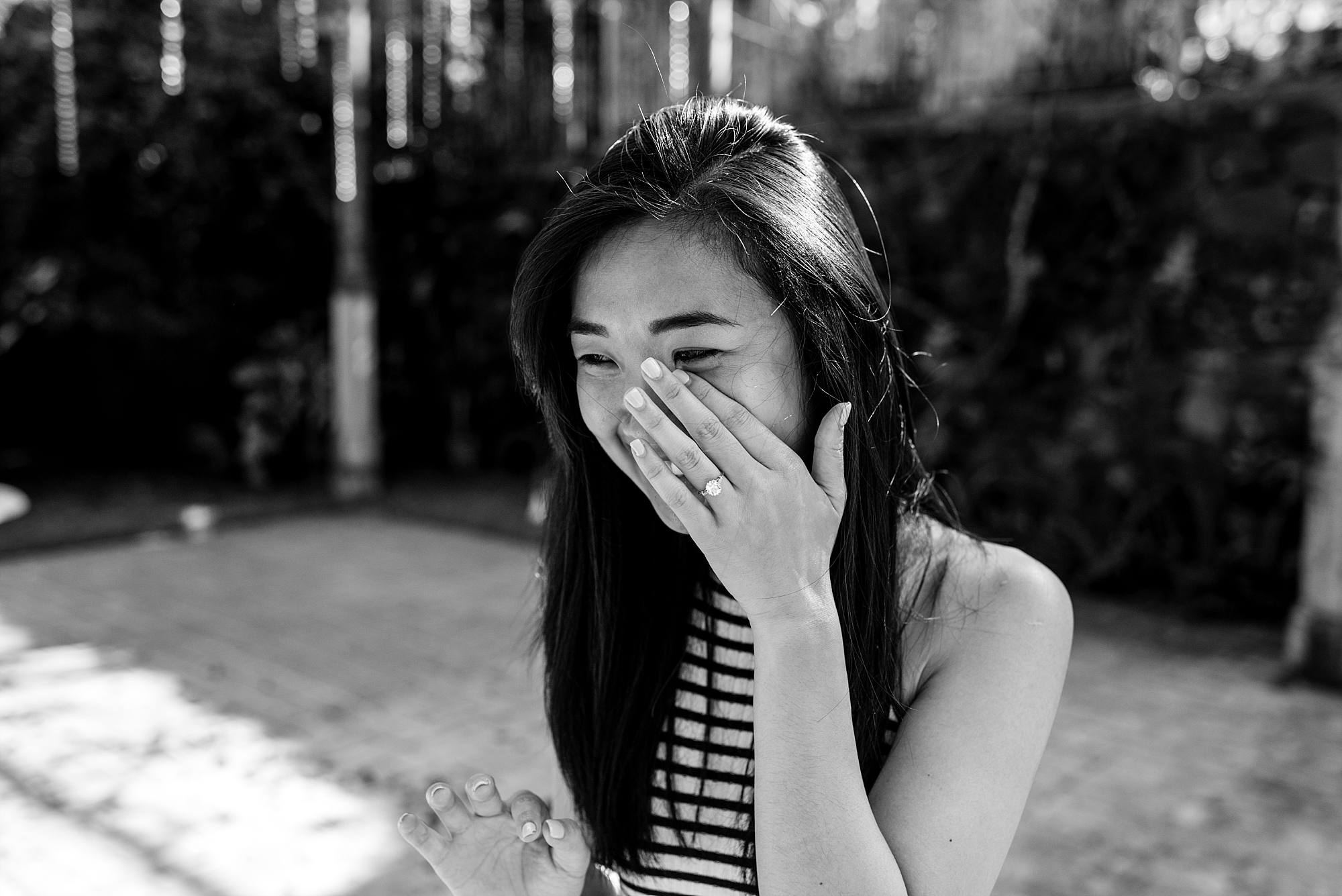 Woman crying with joy hand at her face with a new diamond on it