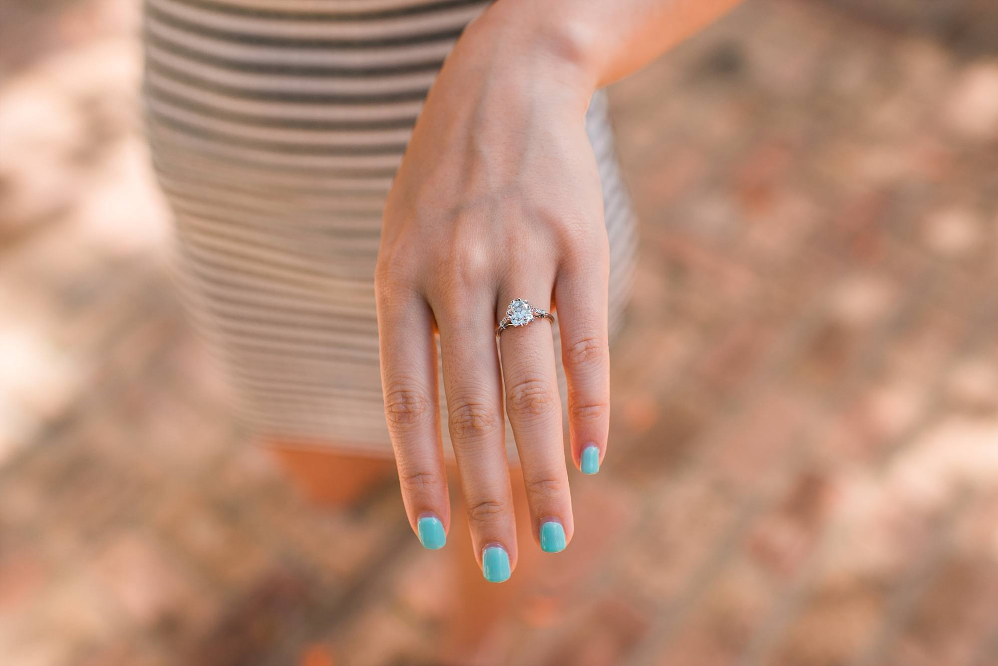 Newly engaged woman showing off her hand with her engagement ring on it