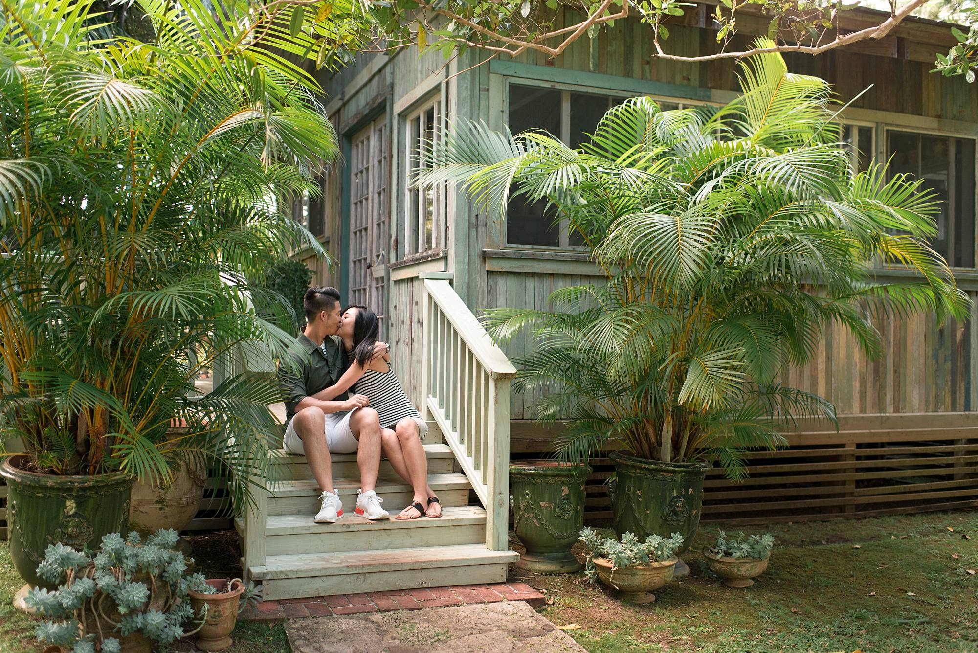 engagement photo of woman and man kissing on wooden stairs next to a small room at the Haiku Mill