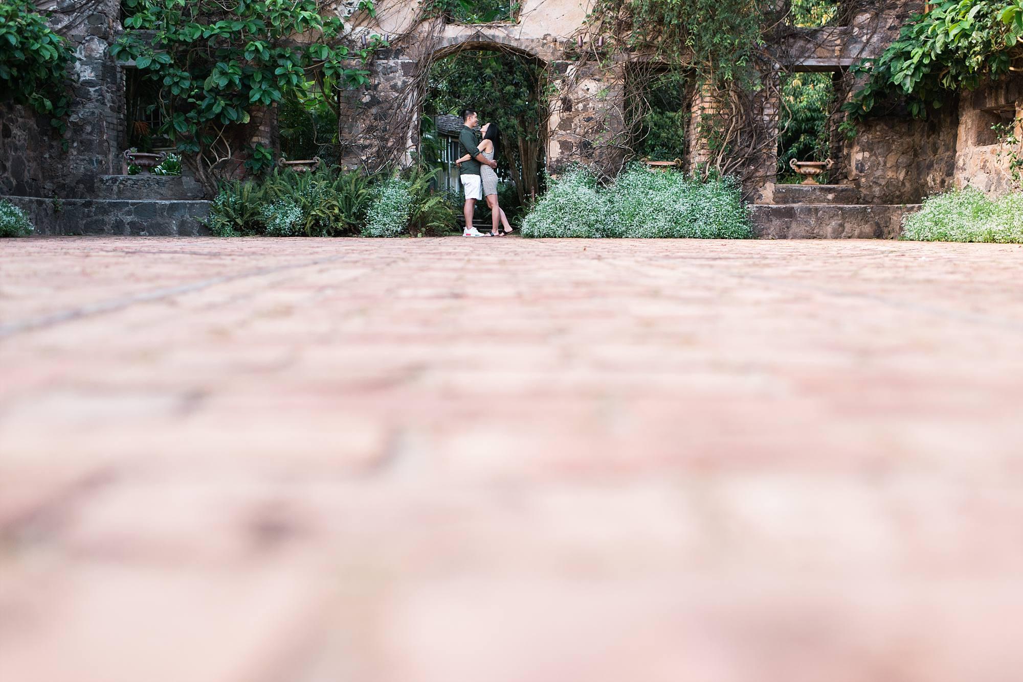 Fiances standing insisde stone arch-doorway at haiku Mill
