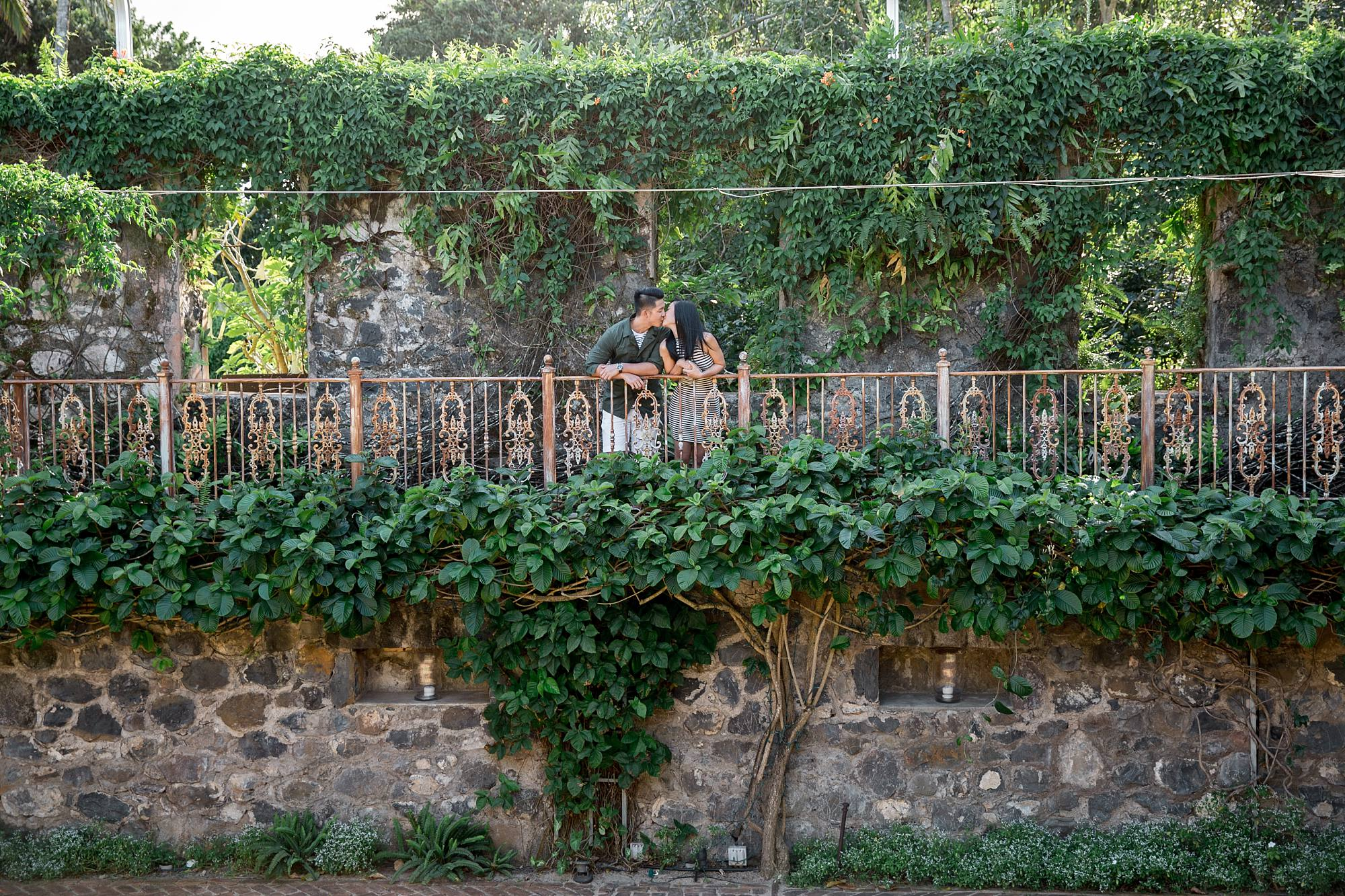 Fiances kissing on top of stone walkway with beautiful greenery