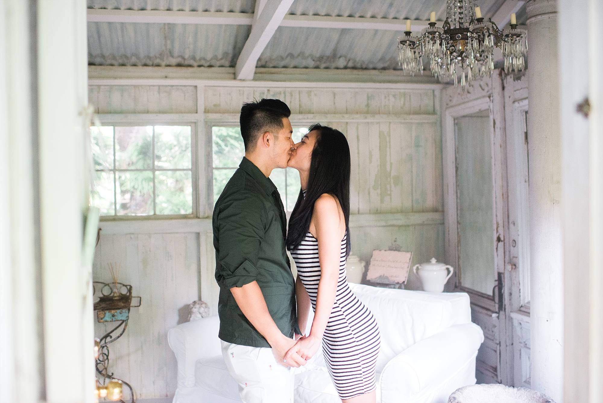 a sweet kiss between new fiances in a rustic white room