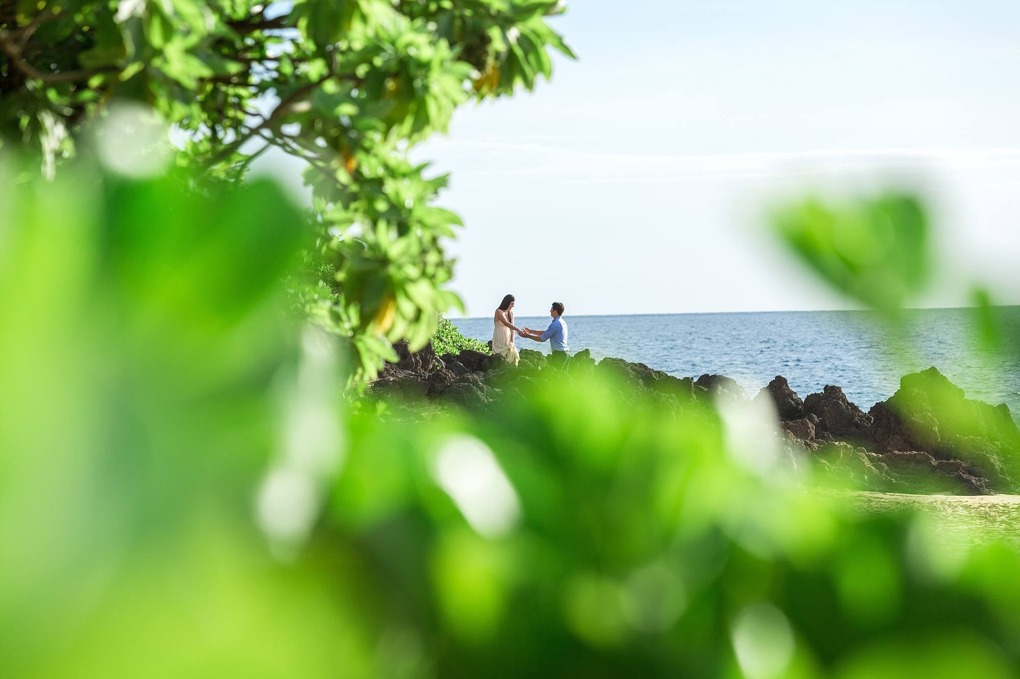 sneaky shot of couple entering beach over lava rocks