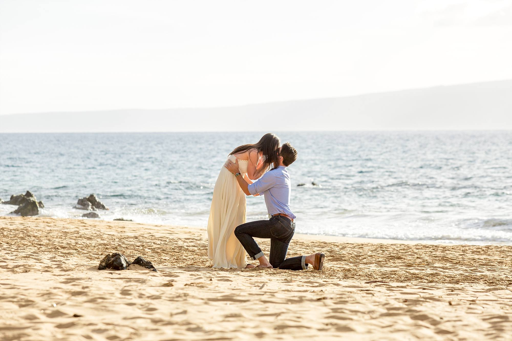 woman bending down to kiss her brand new fiance as he's on one knee