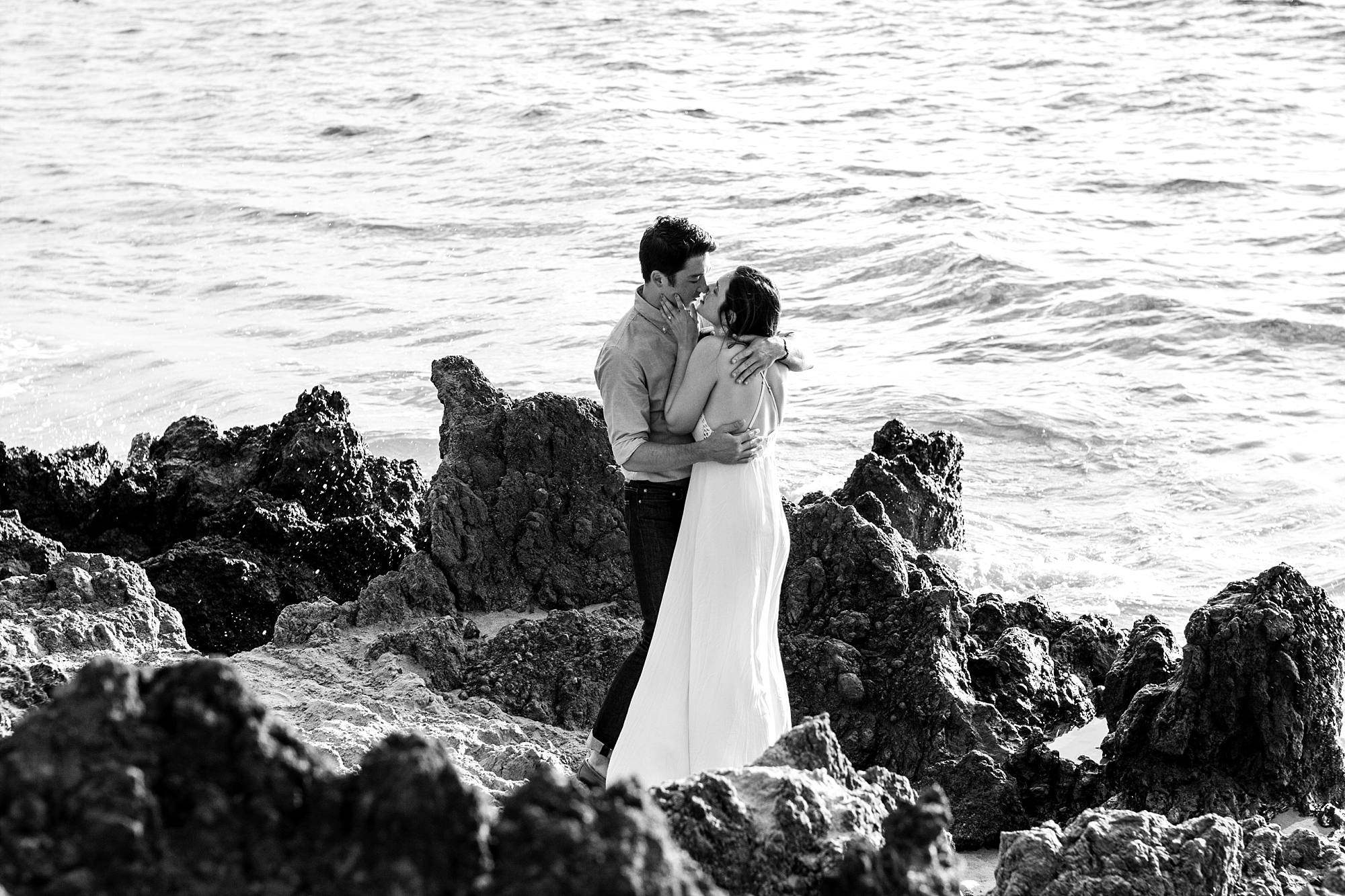 black and white image of couple wrapped in each others arms on Maui's lava rocks