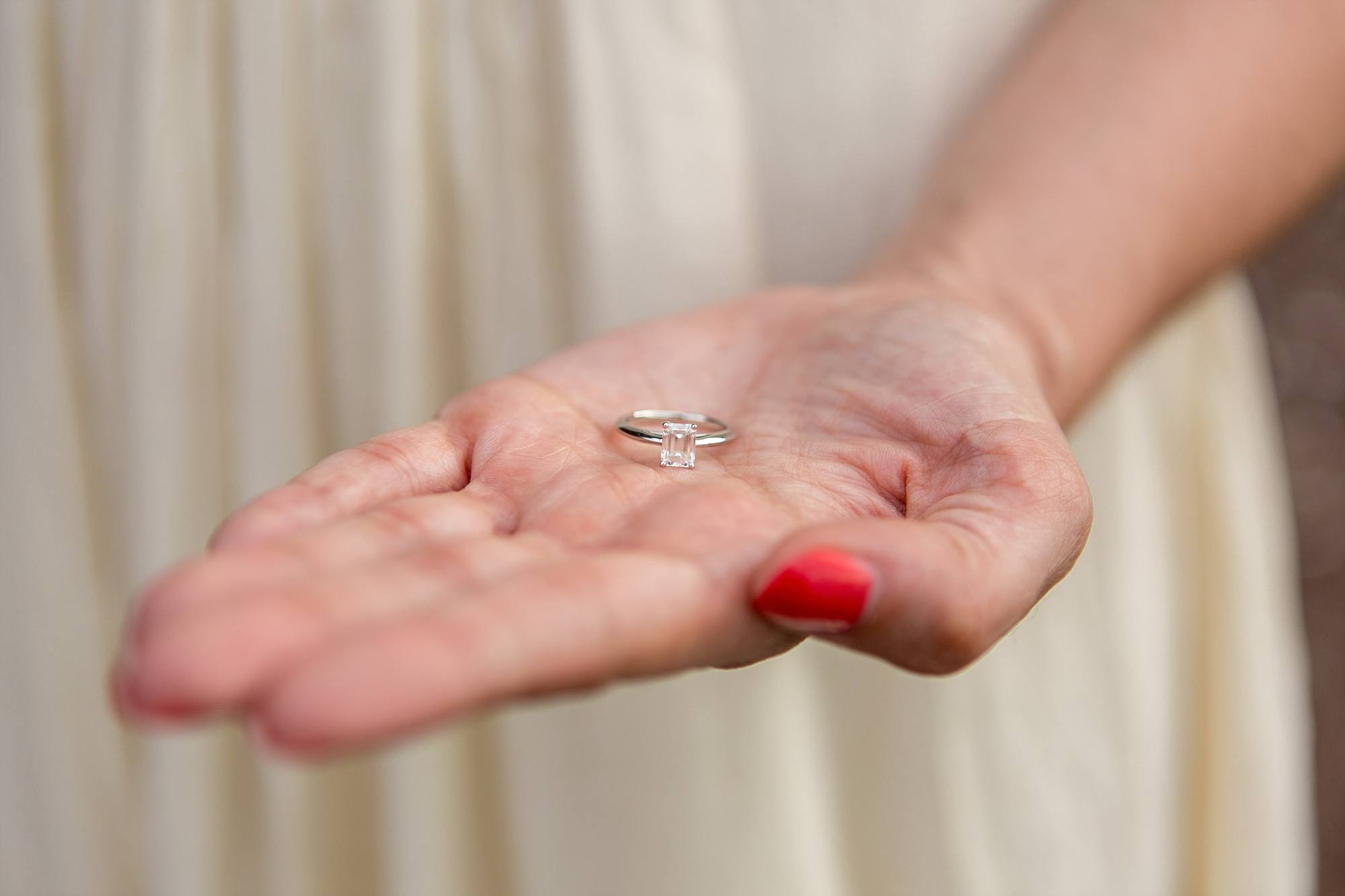 gorgeous emerald cut diamond engagement ring in bride to be's hand