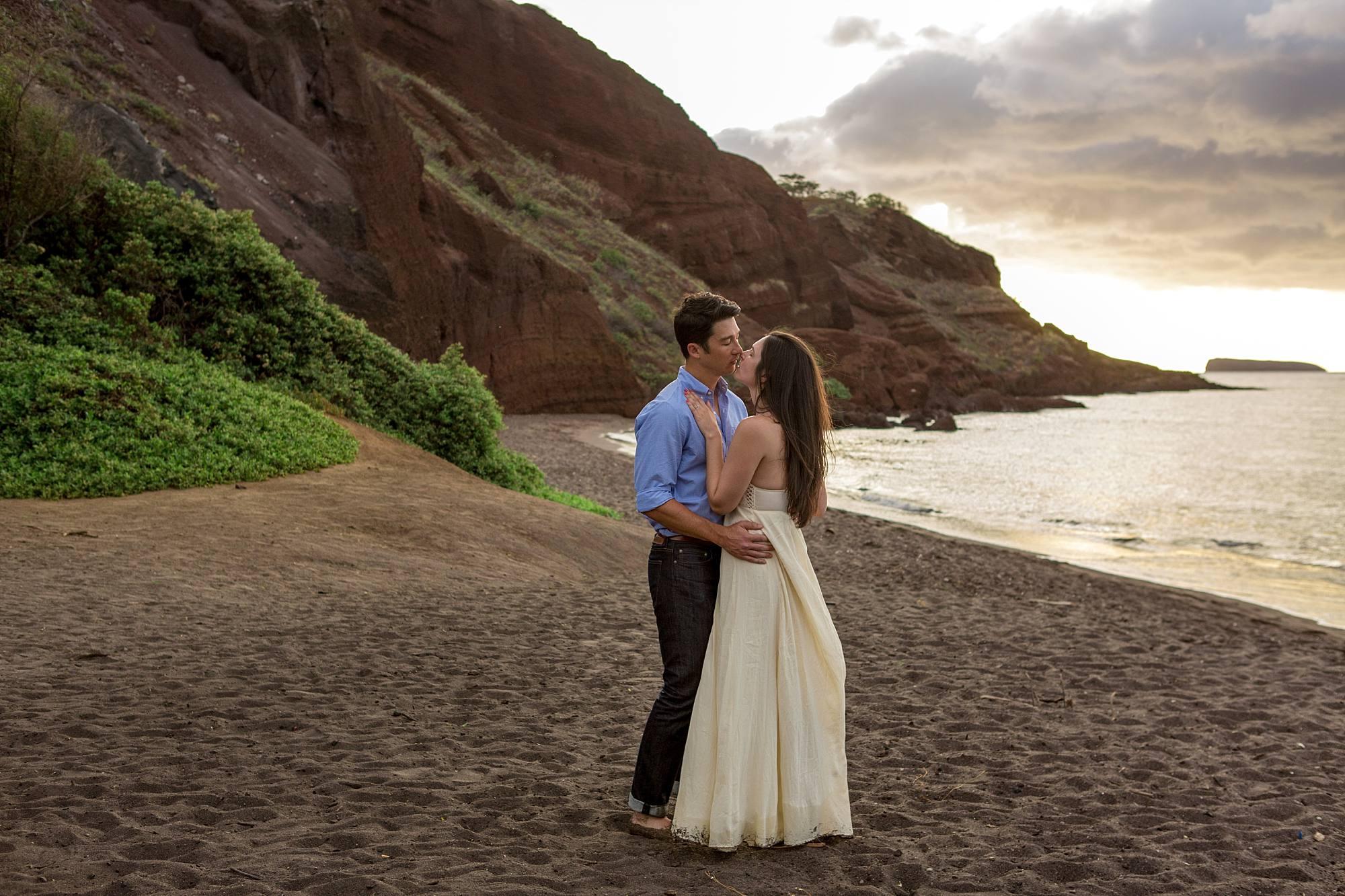 incredible Maui rock wall behind newly engaged couple kissing