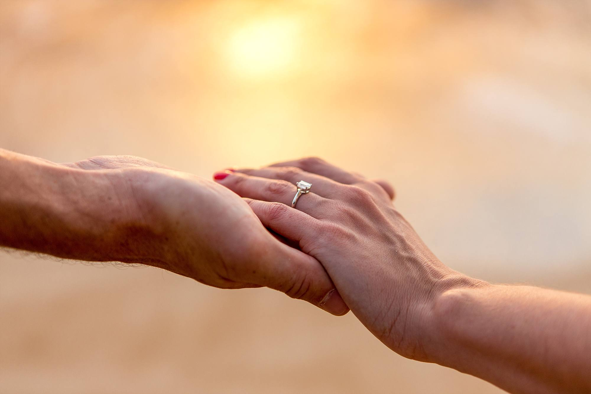 beautiful engagement ring on woman's hand, she's hand in hand with fiance