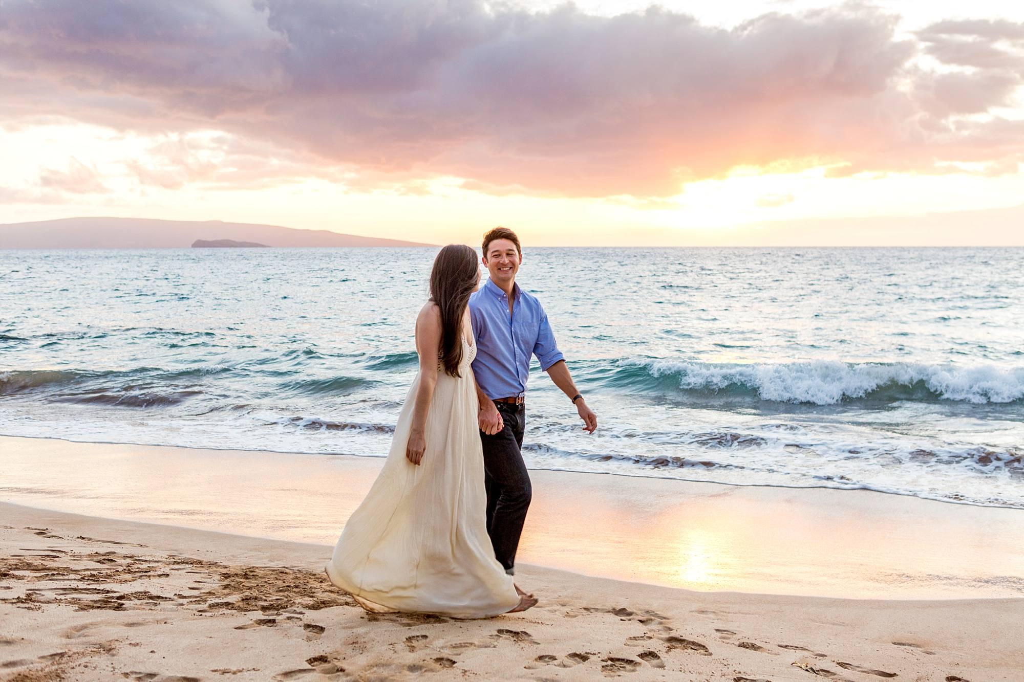 Engagement portrait sunset couple walking down beach