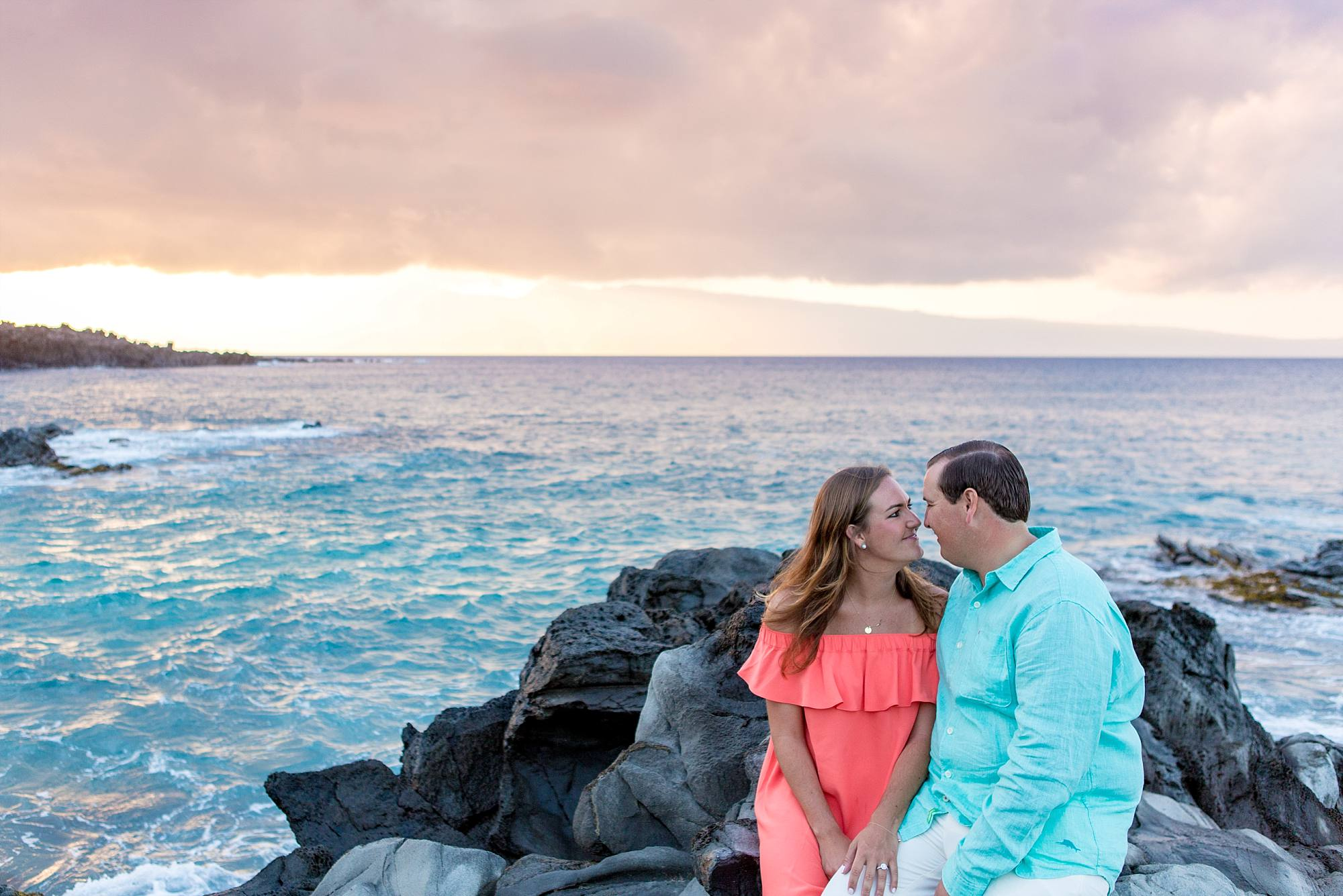 fiances gazing into each others eyes sitting on Maui lava rocks