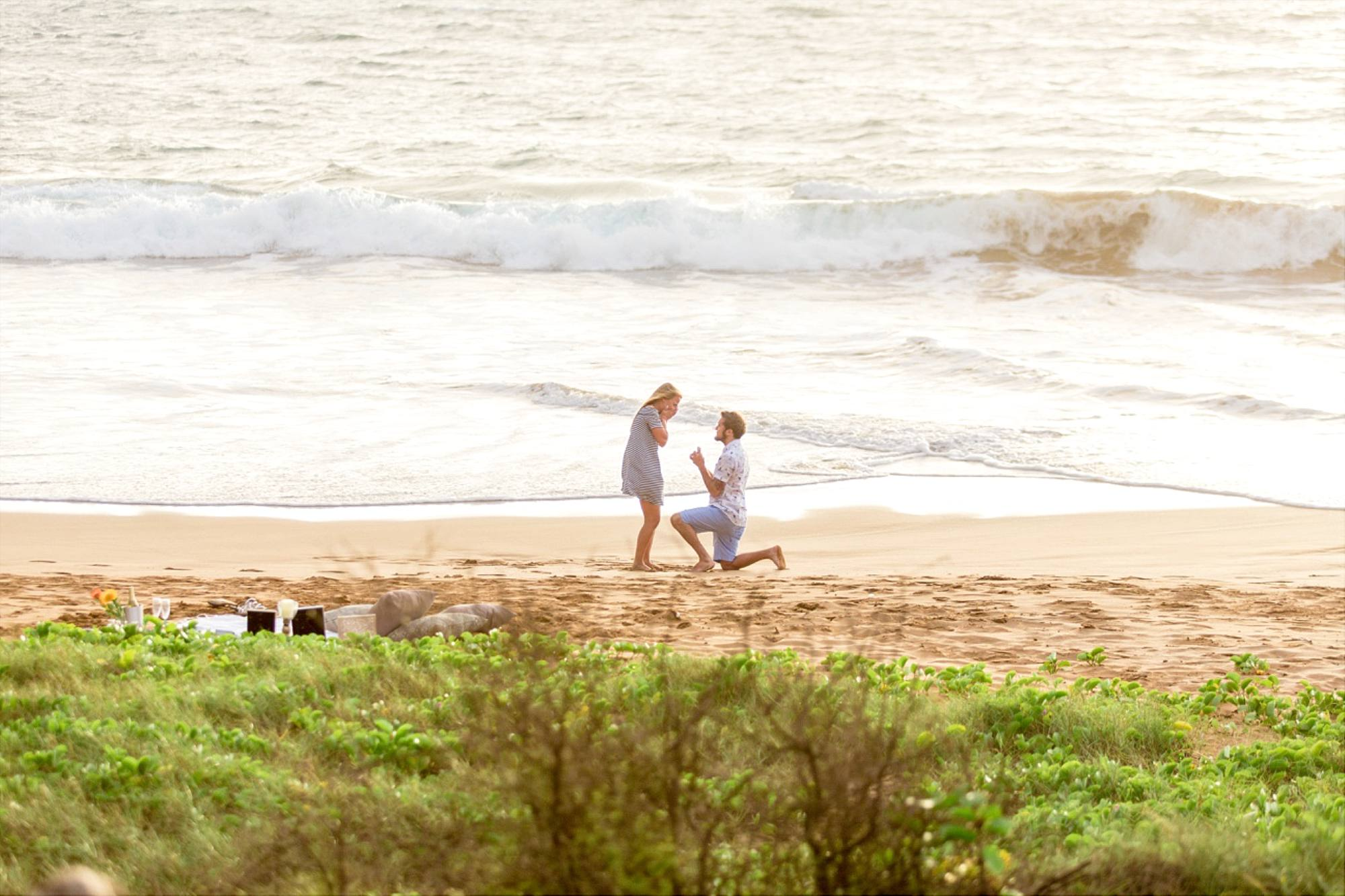 man down on one knee proposing on Maui beach