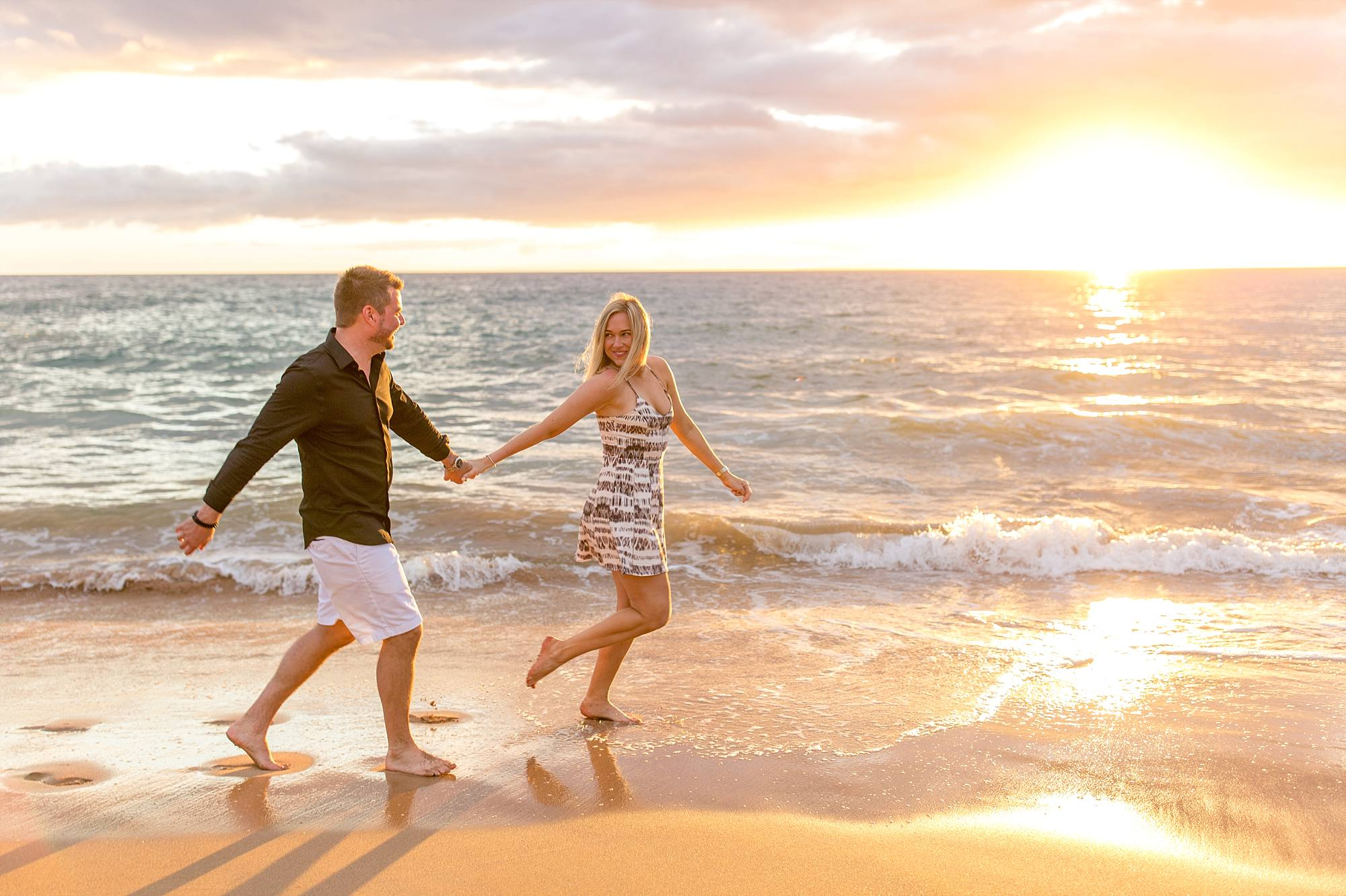 fiances running down beach together hand in hand and the way she's looking at him is full of love