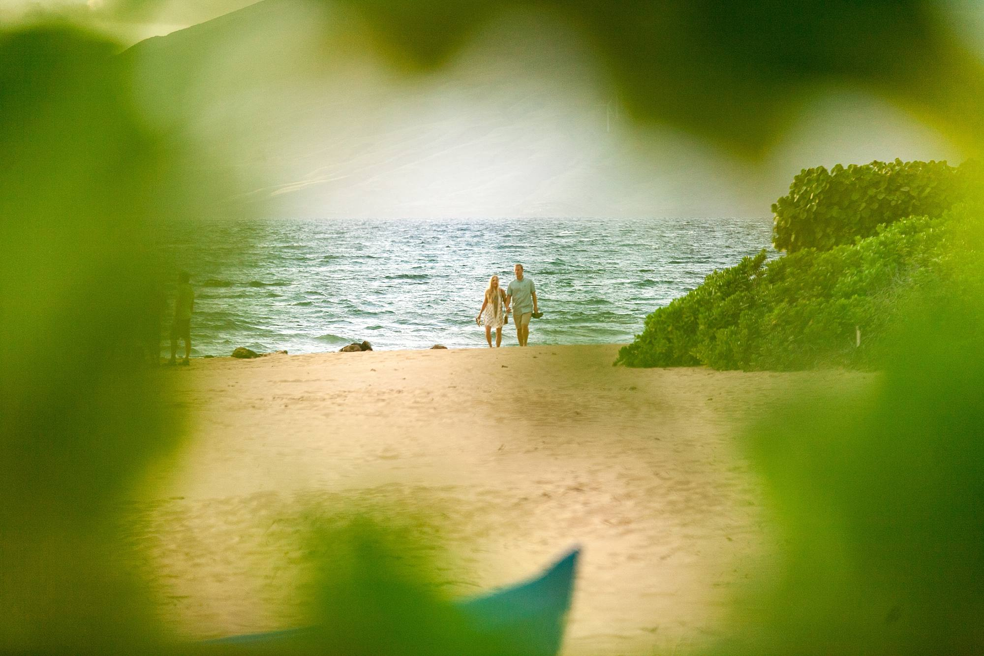 shot framed with greenery as photographer hides in bushes to capture their engagement