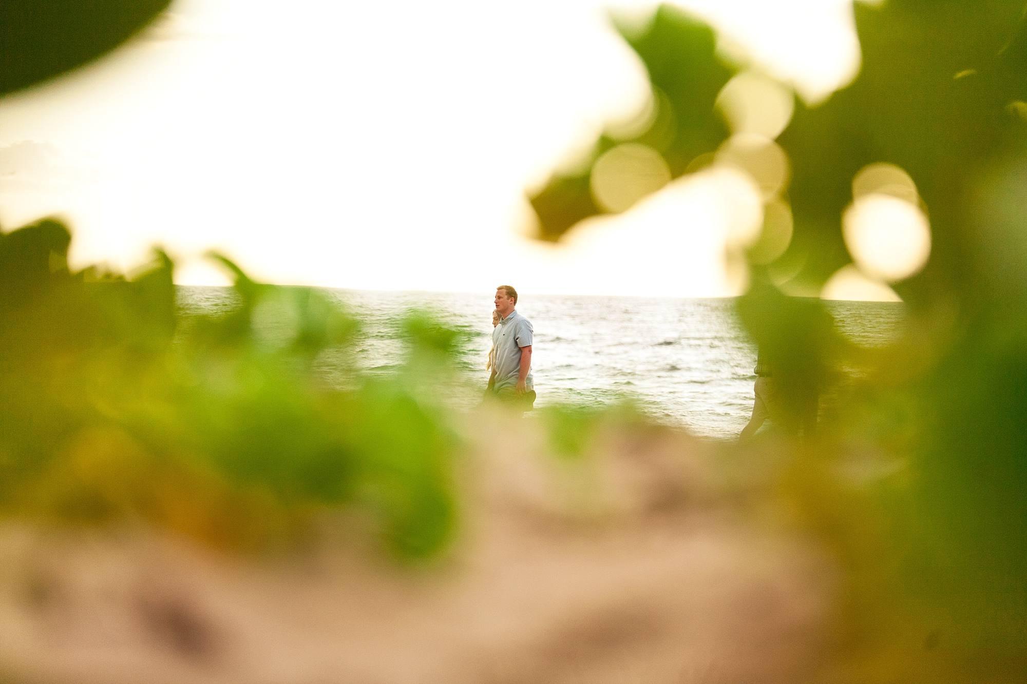 sneaky shot of couple walking along the beach, shot through the bushes