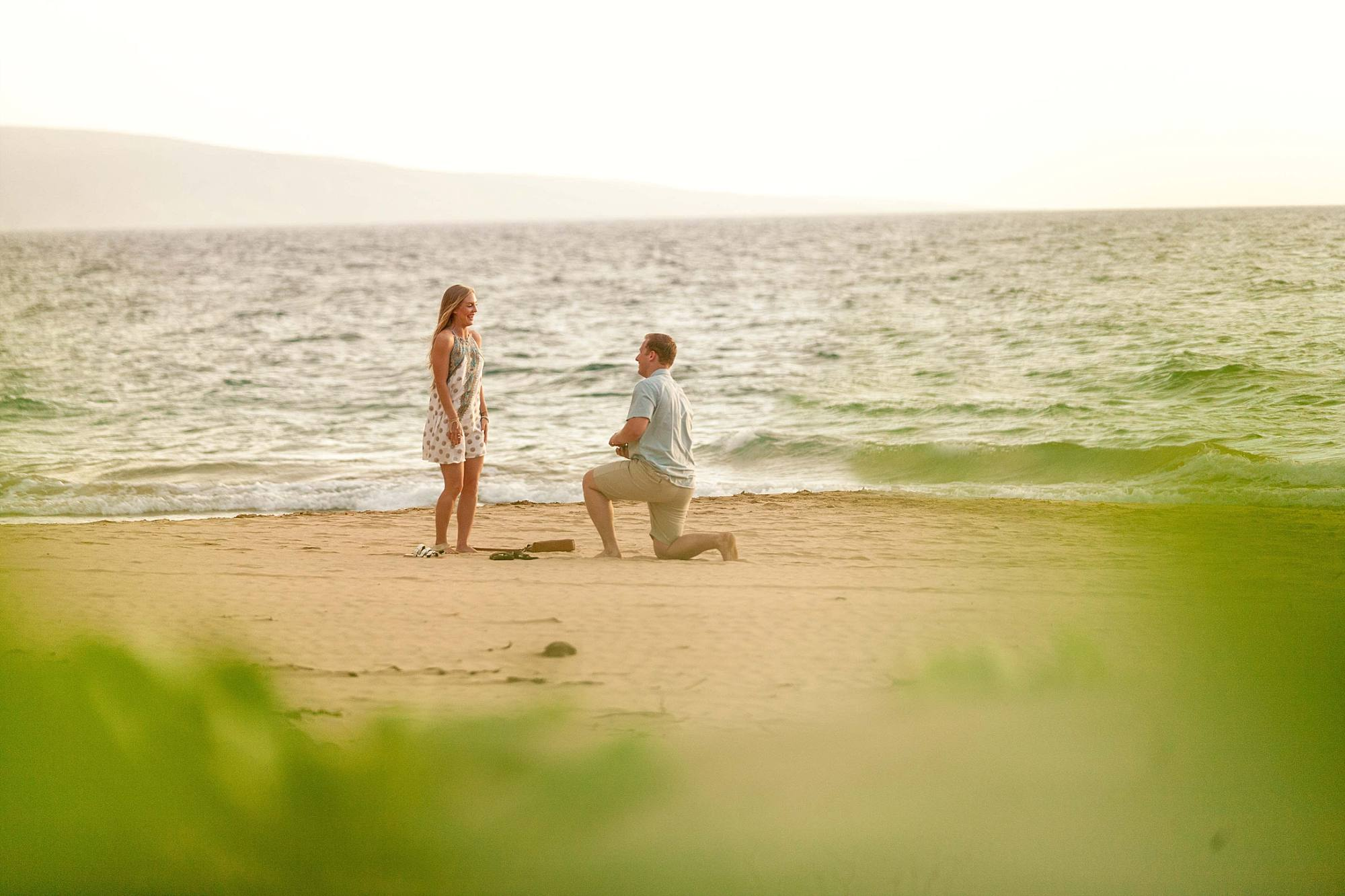 man down on one knee proposing to his girlfriend on Maui
