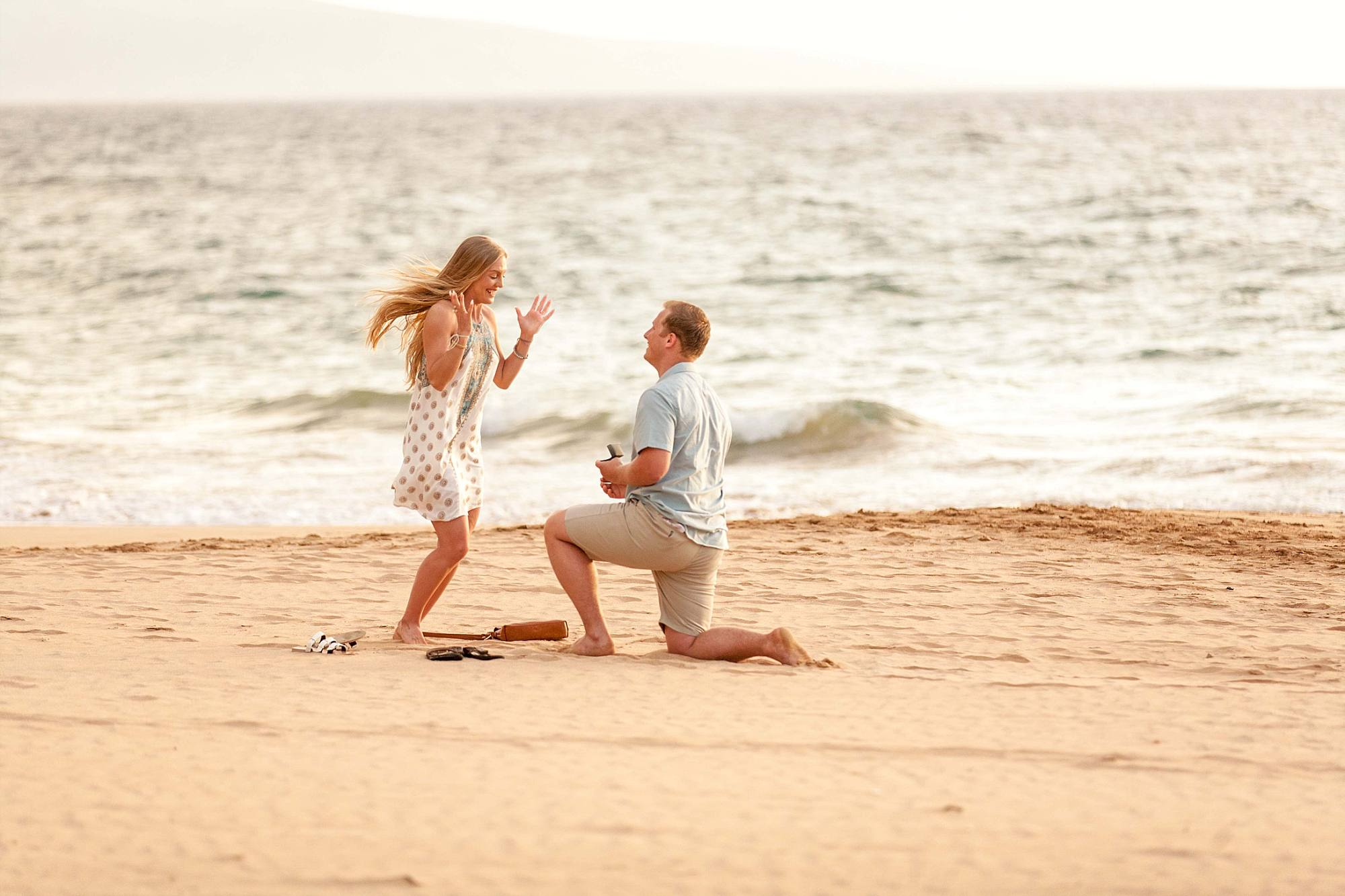 woman jumping for joy as boyfriend proposes to her on the beach