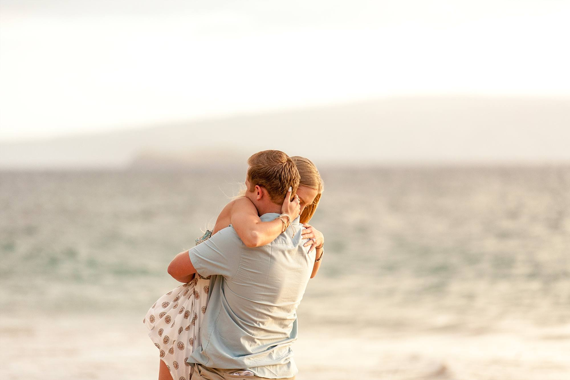 man lifting woman up and spinning her in a hug with the ocean behind them