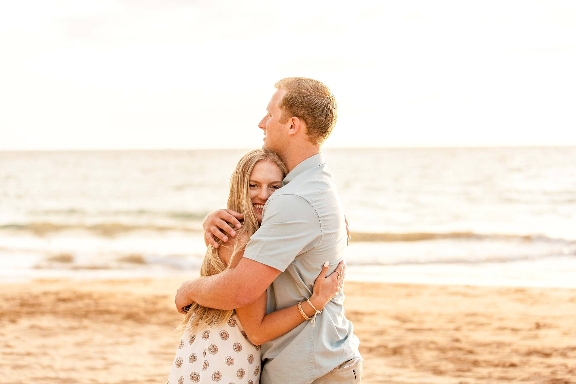 woman absolutely glowing after a proposal getting hugged by her new fiance