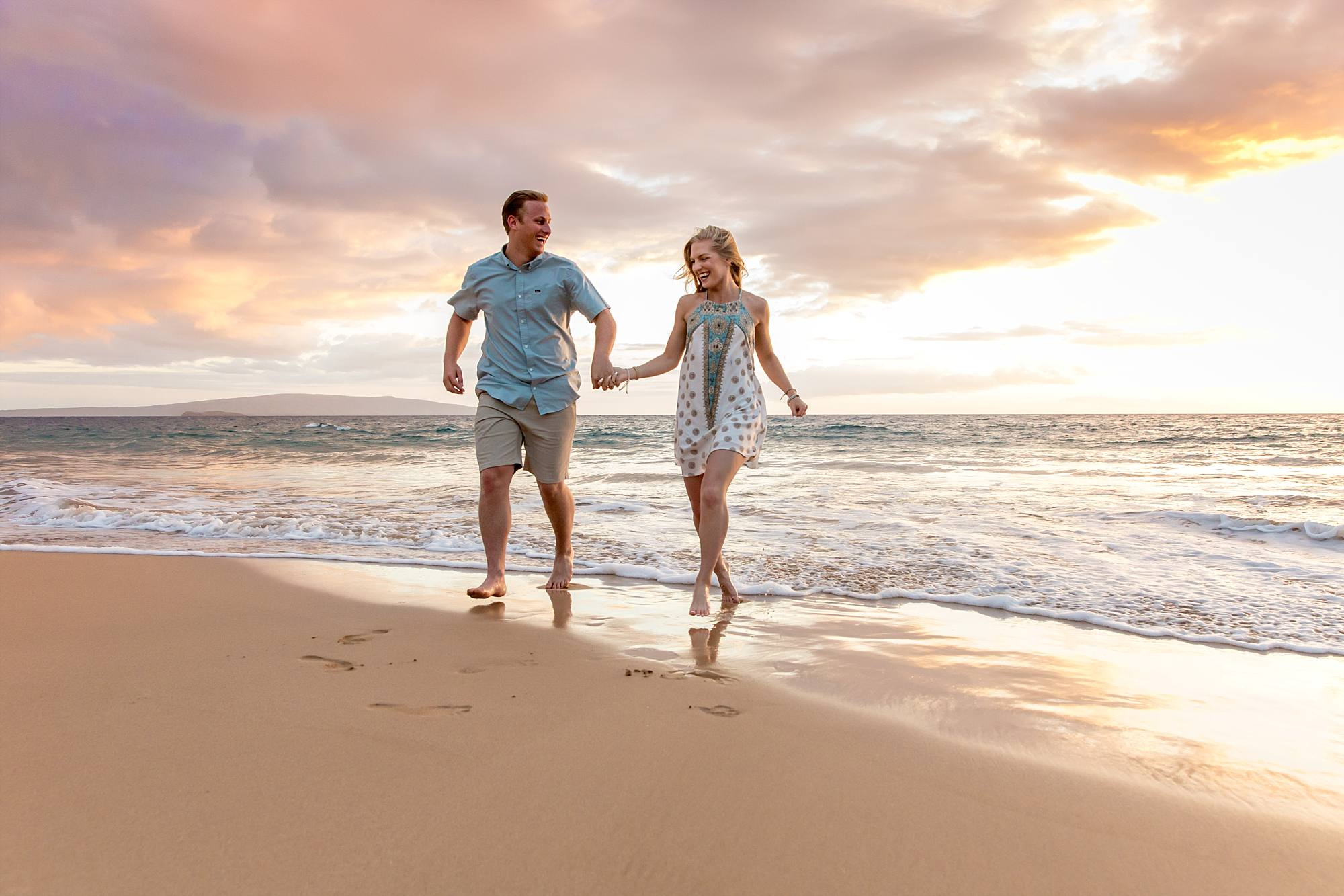 future bride and groom walking hand in hand in the water with a beautiful Maui sunset behind them