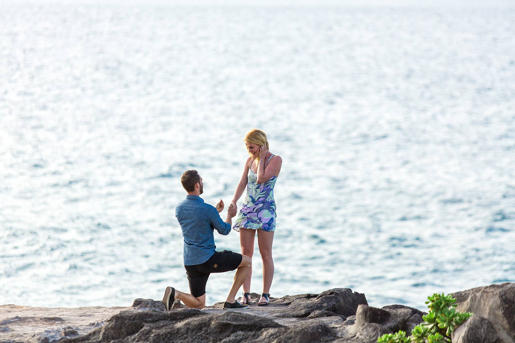 man down on one knee proposing to girlfriend with gorgeous Maui water behind them
