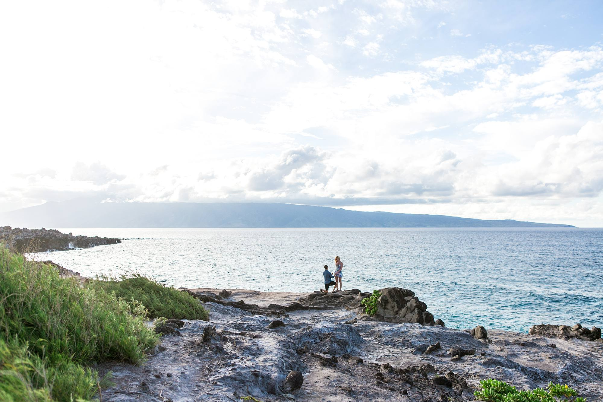 beautiful wide shot of couple during proposal with incredible view of Northwest Maui