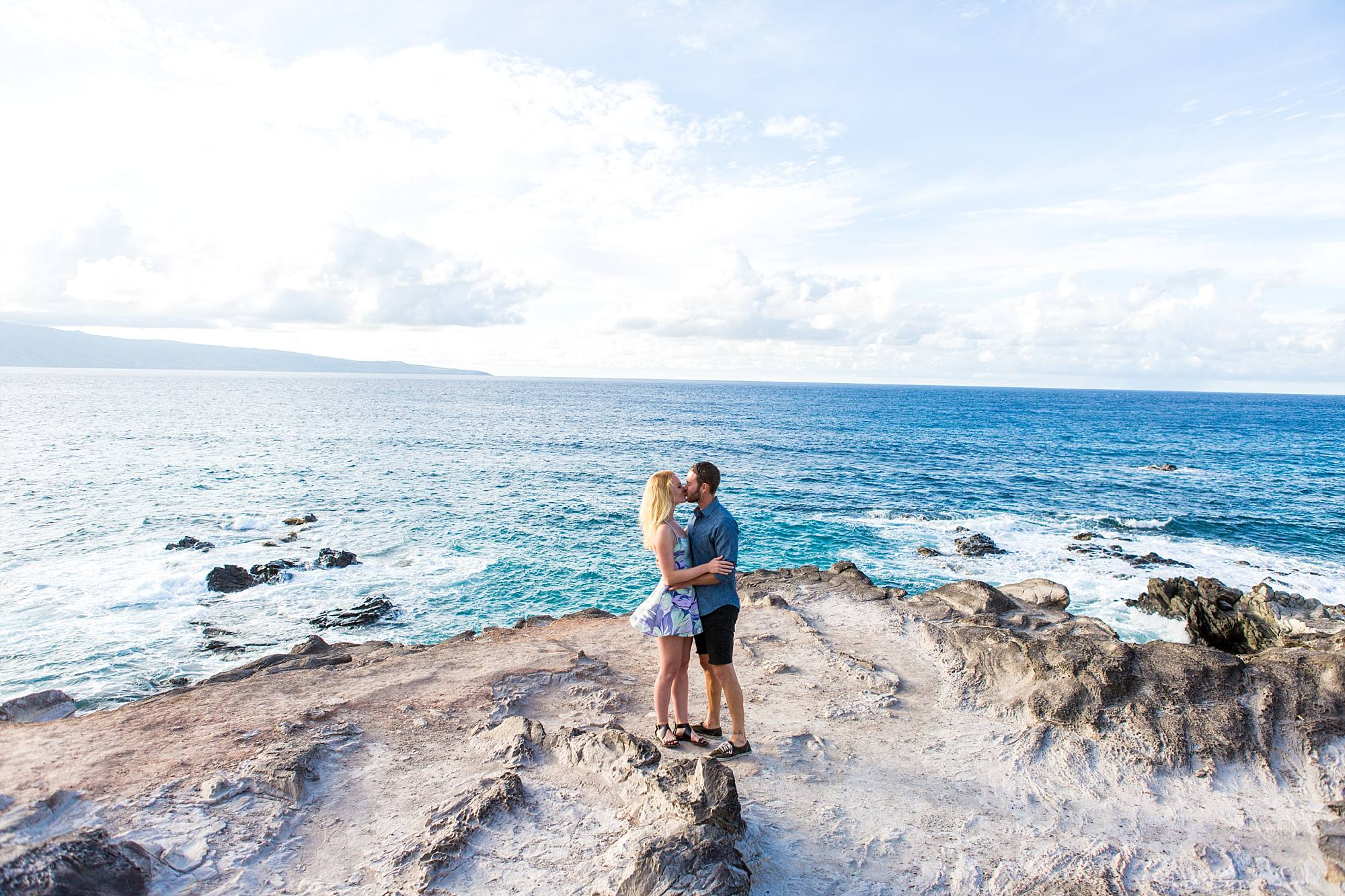 the bright blue water of Maui surrounding the couple standing and kissing on a cliff