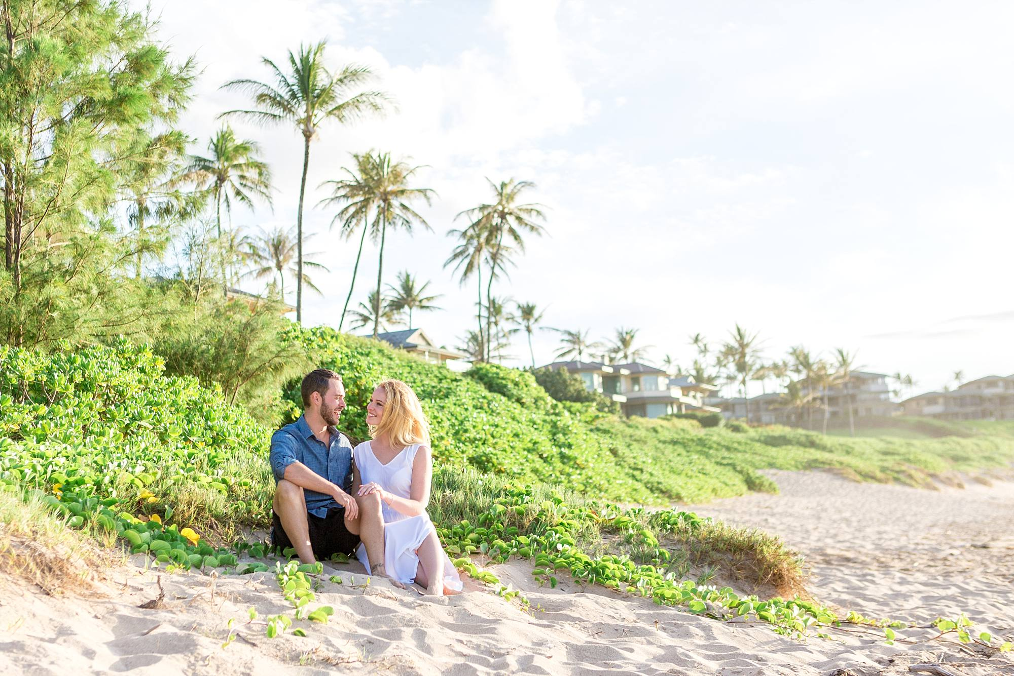 couple canoodling in the sand with bright greenery surrounding them