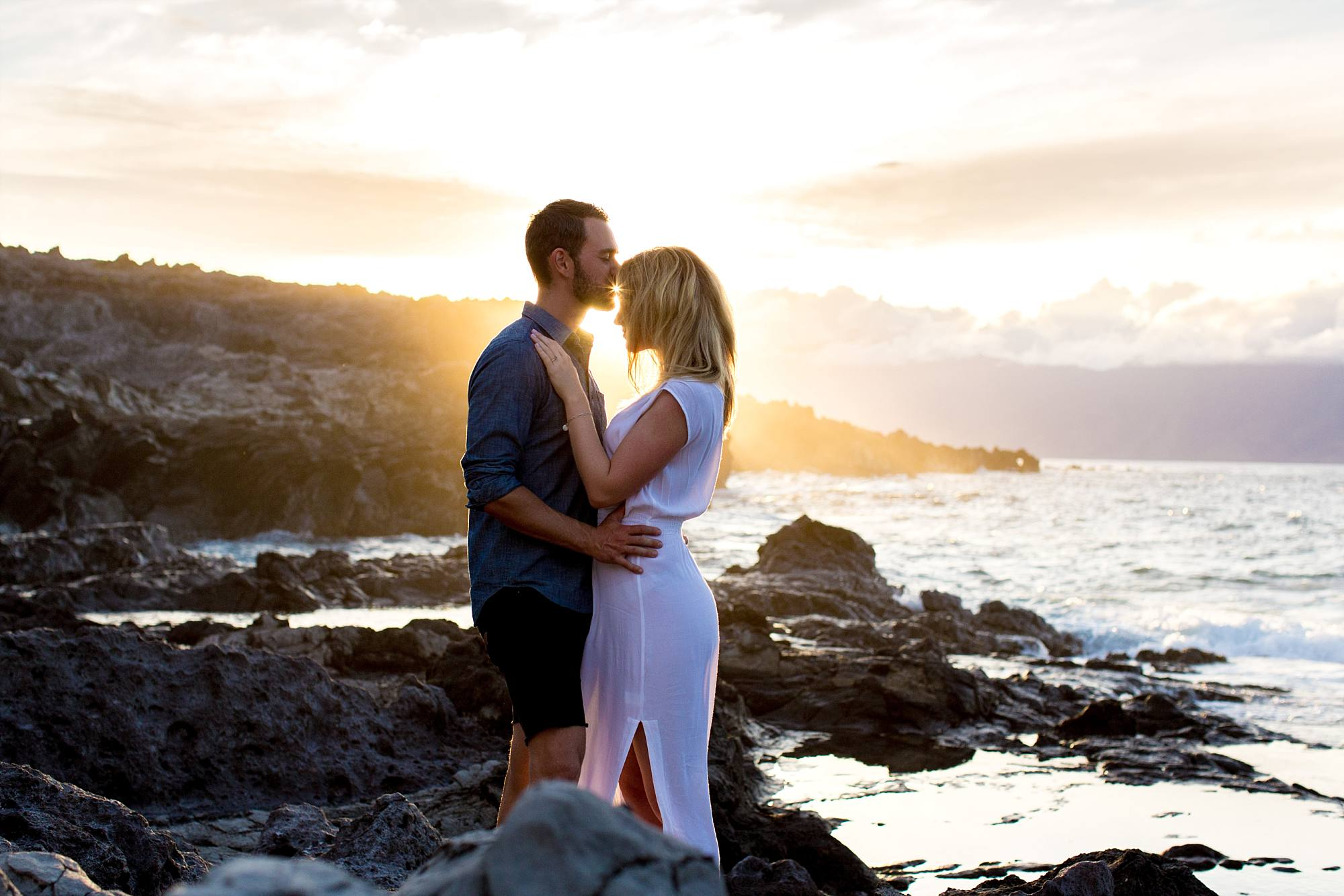 incredible Maui sunset on the cliffs, engaged couple cuddling together