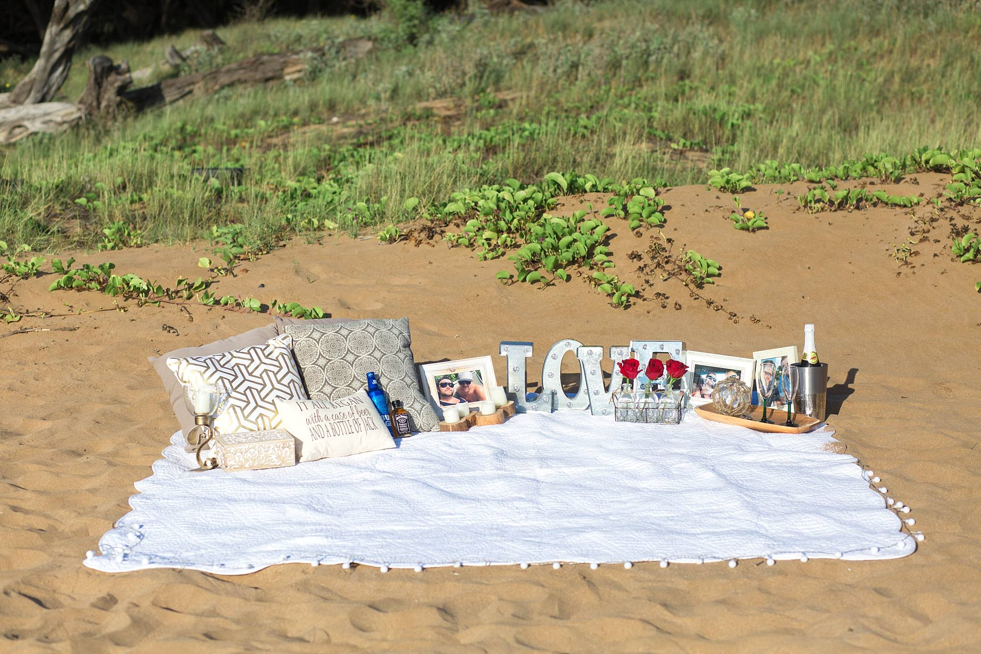 Proposal picnic in the sand set up with LOVE spelled out, blanket, pillows
