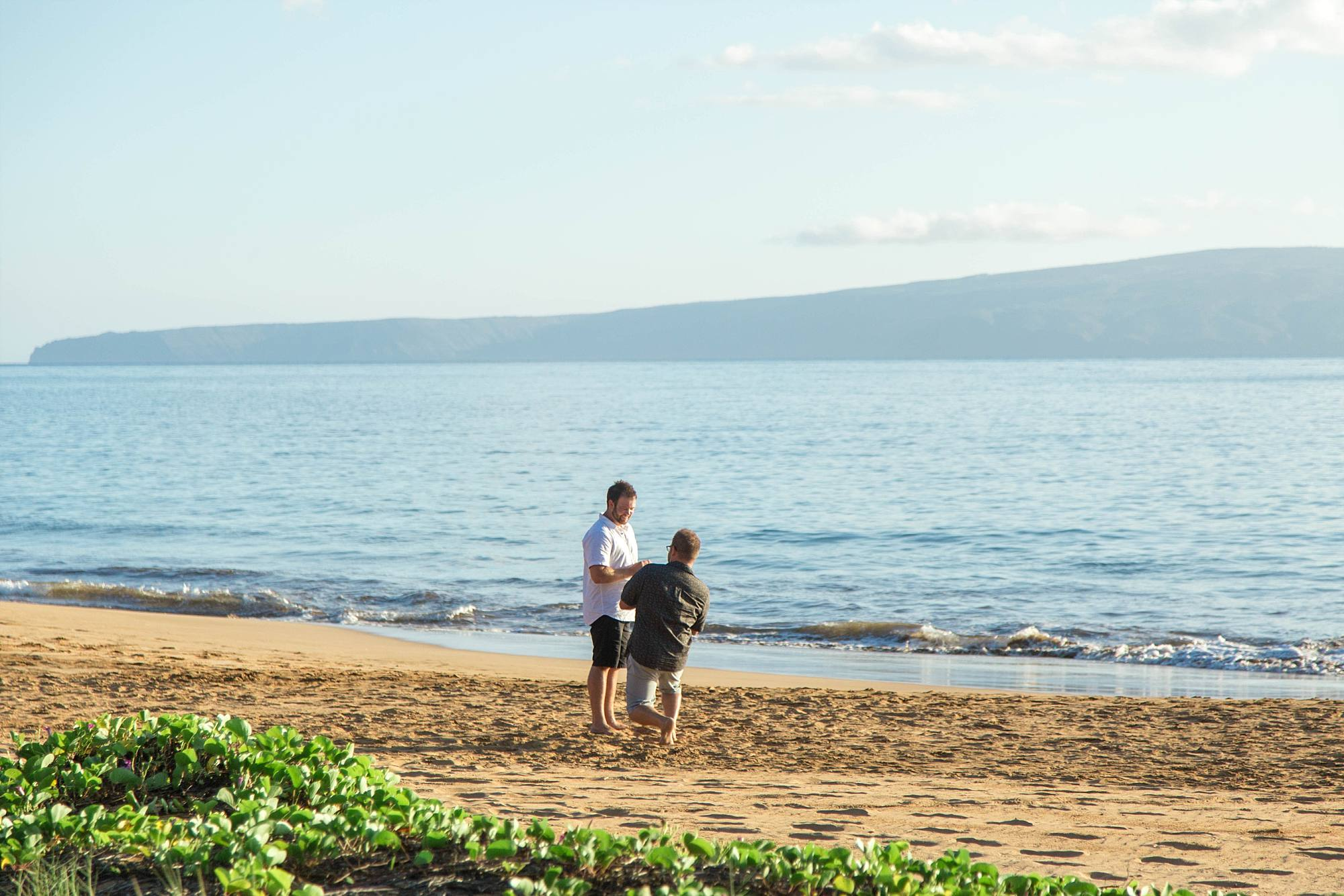 same sex picnic proposal on Maui, man bending down to kneel in the white sand asking his love to marry him