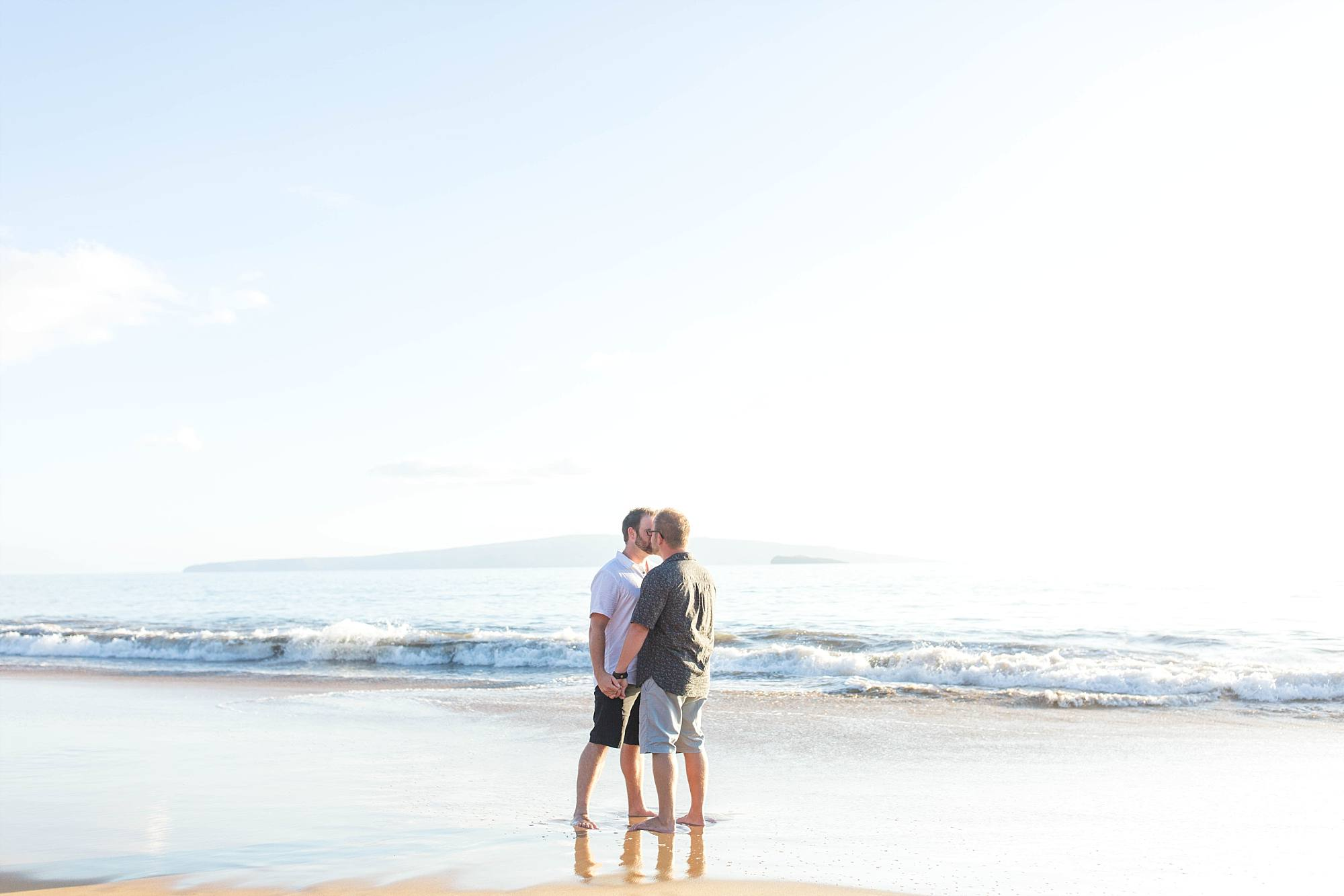 the newly engaged couple is sharing a sweet kiss at the waters edge, waves rolling in