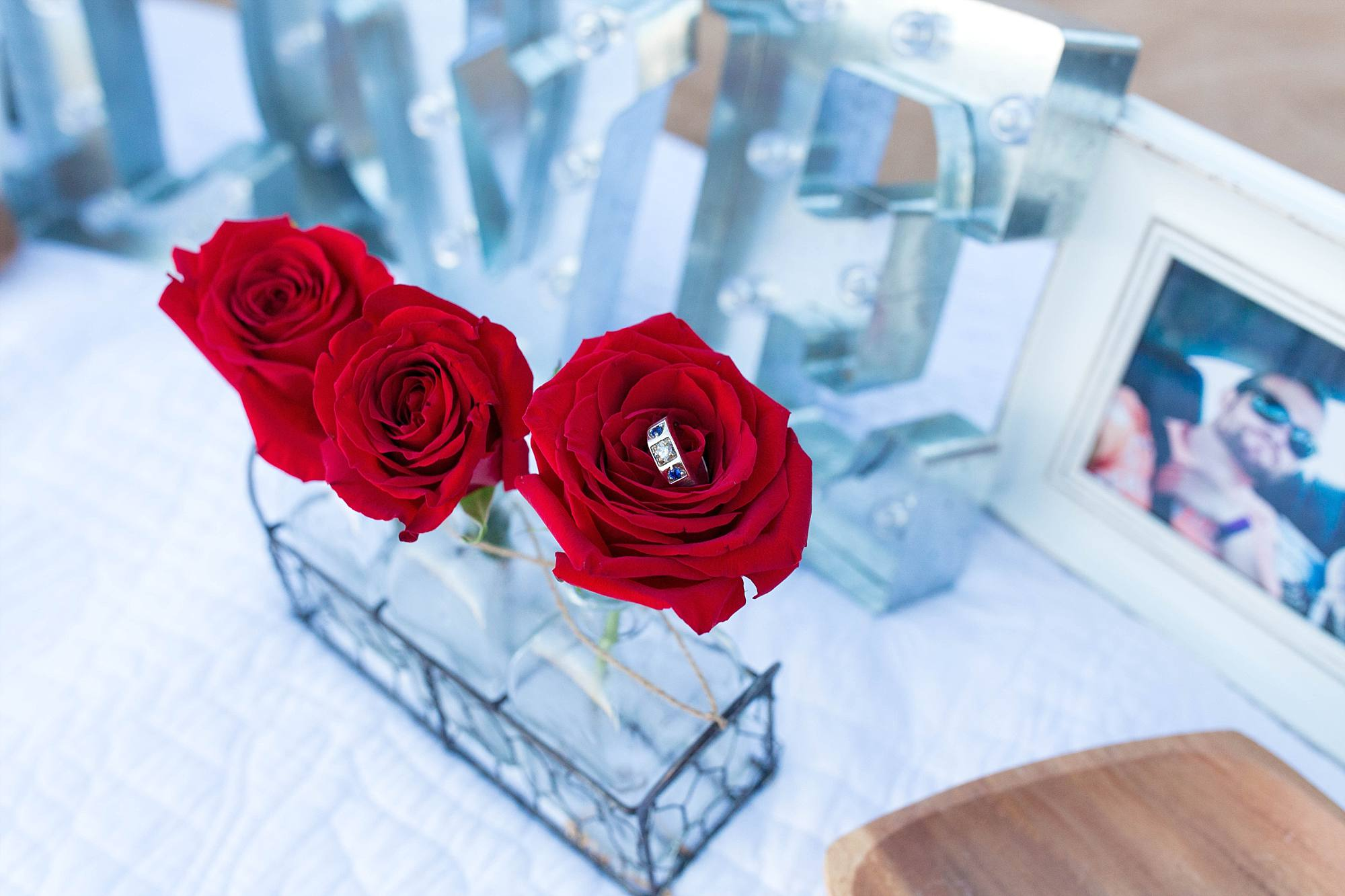 men's diamond engagement ring showcased in a red rose