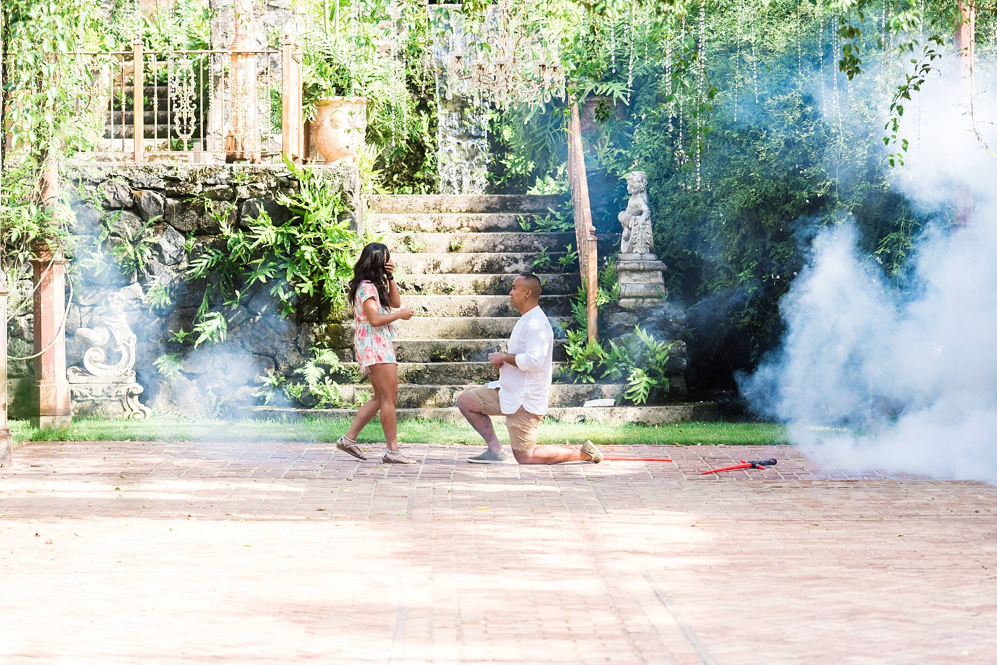 man proposing to his girlfriend at haiku mill, stairs in the background and smoke from smoke machine