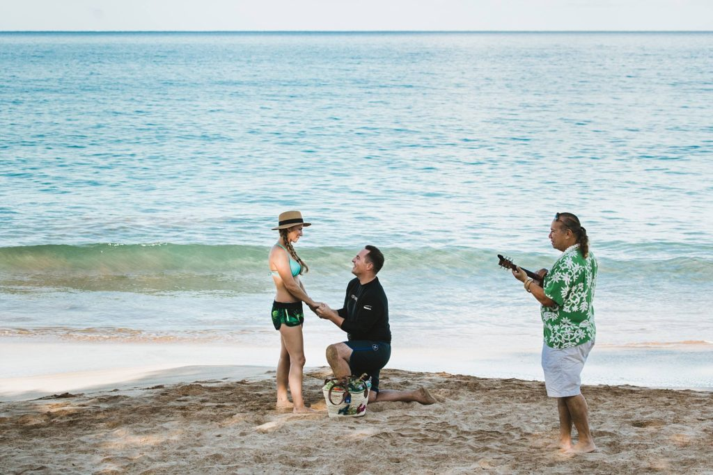 man down on one knee proposing to his girlfriend on Maui's South Shore with ukulele player Charles Nahale serenading them