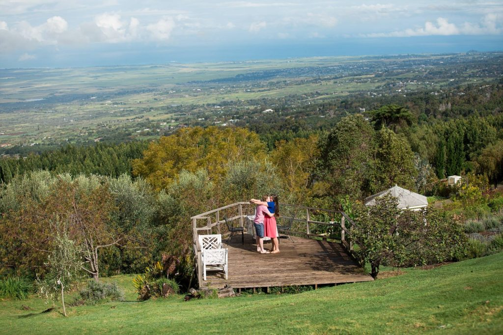 couple kissing on deck that looks down on the valley of Maui