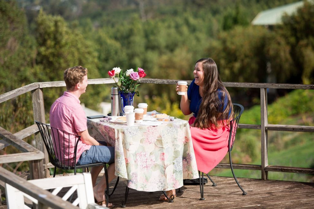 happy lovebirds laughing together at a private picnic at the lavender farm on a wooden deck