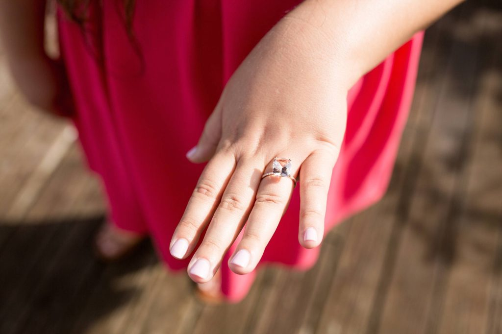 woman showing off her ring with perfectly manicured nails