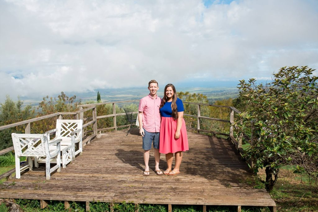newly engaged couple standing on deck at Ali'i Kula Lavender Farm on Maui overlooking the Maui valley