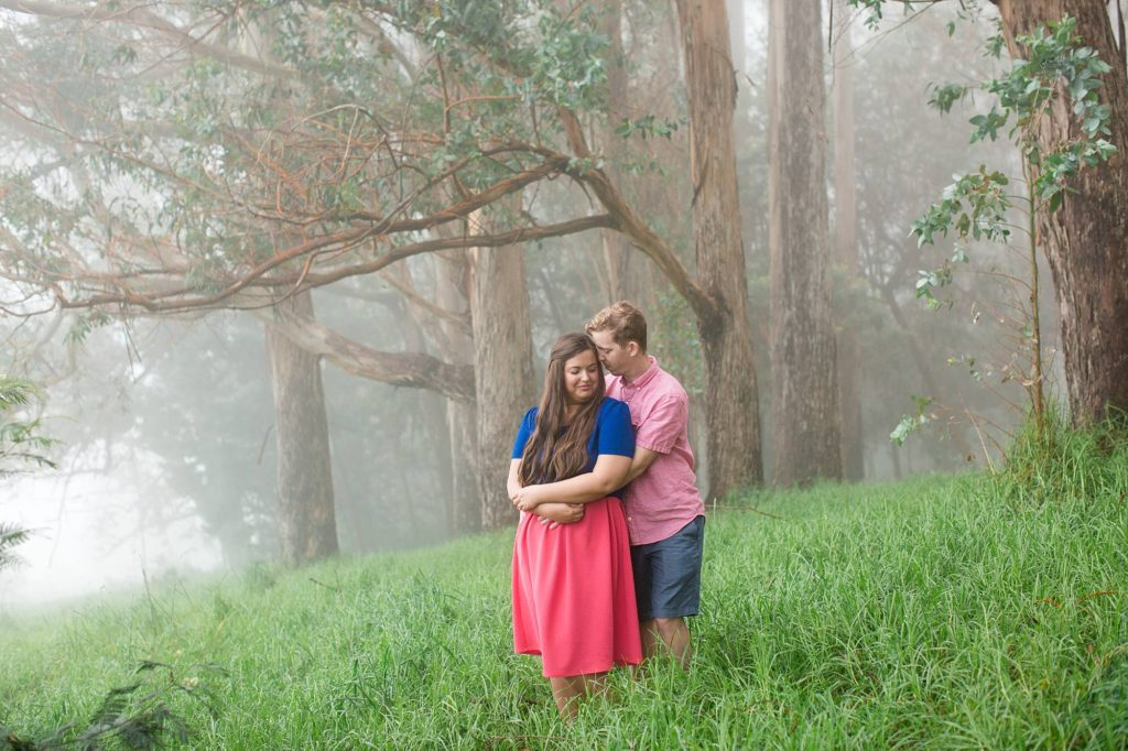 Man with arms wrapped around his bride-to-be on grassy Haleakala with fog rolling in