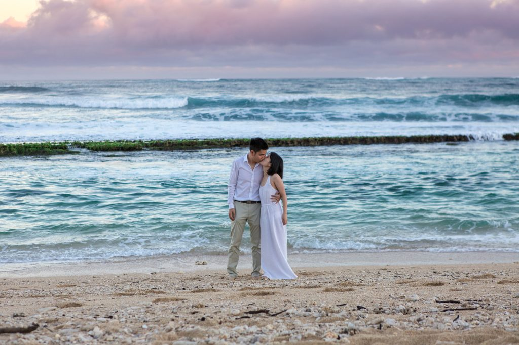 Newly engaged couple kissing at sunrise on Maui beach